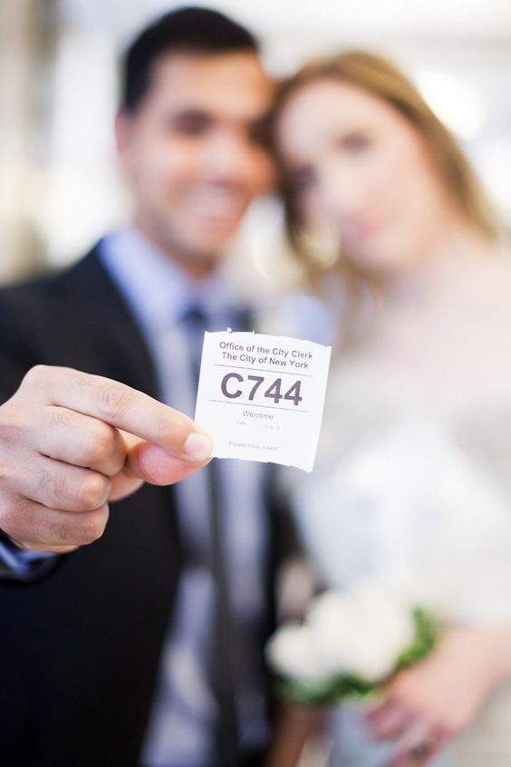 groom holding city hall ticket number showing wedding date