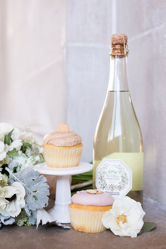 pink frosted cupcakes with champagne bottle and floral decor