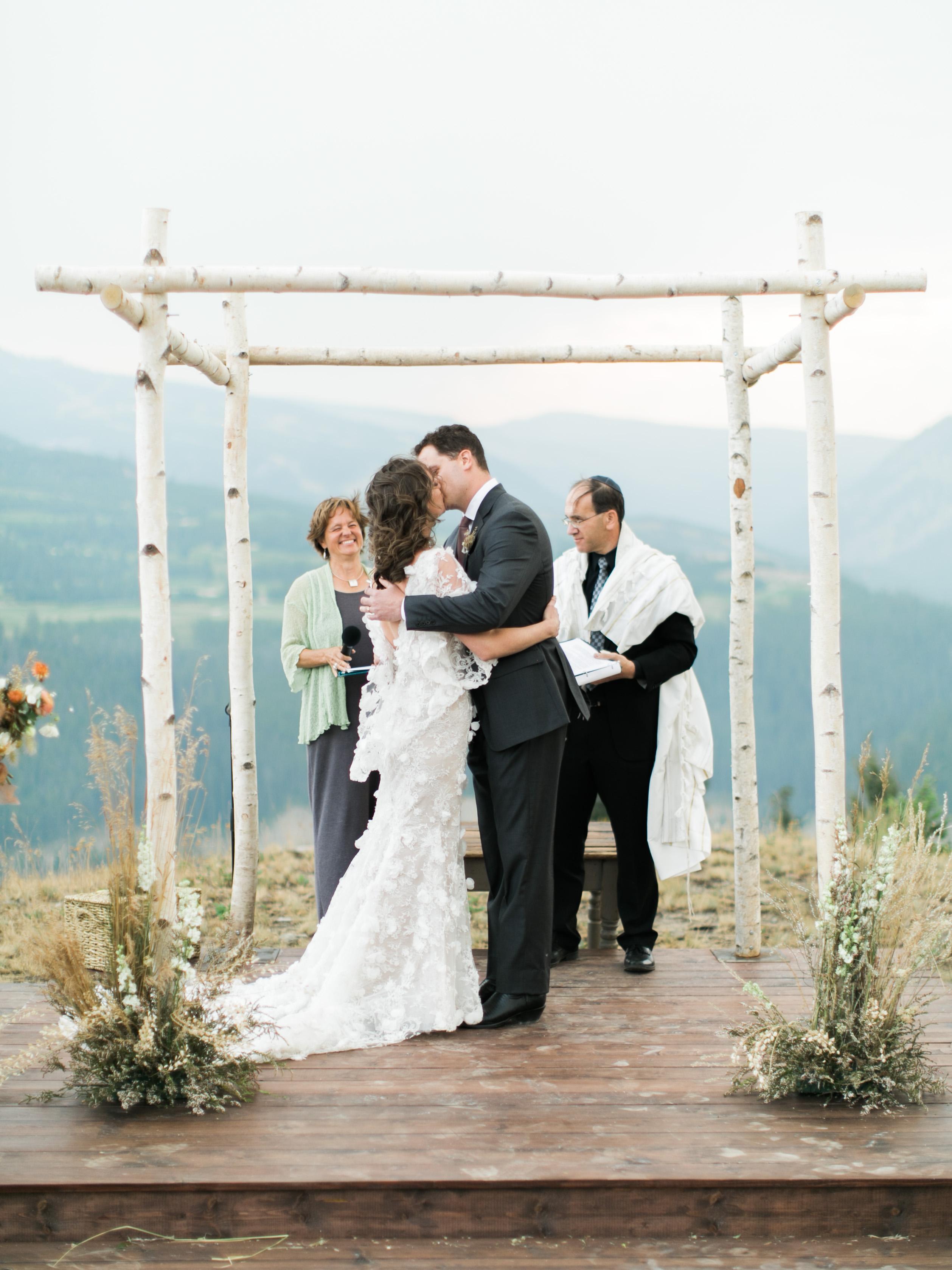 bride and groom standing wedding alter rabbi and spiritual healer