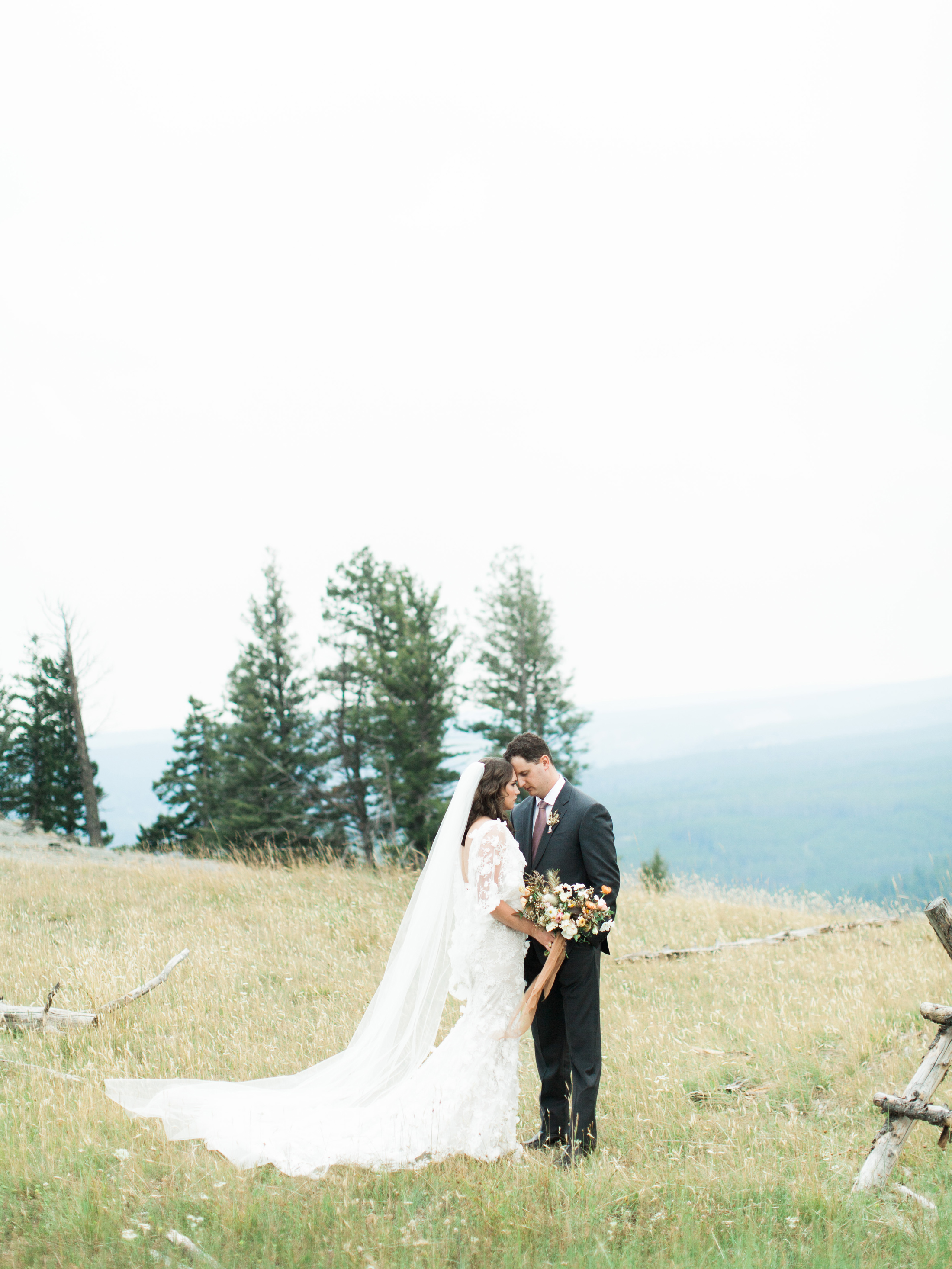 bride and groom facing each other on mountain hillside