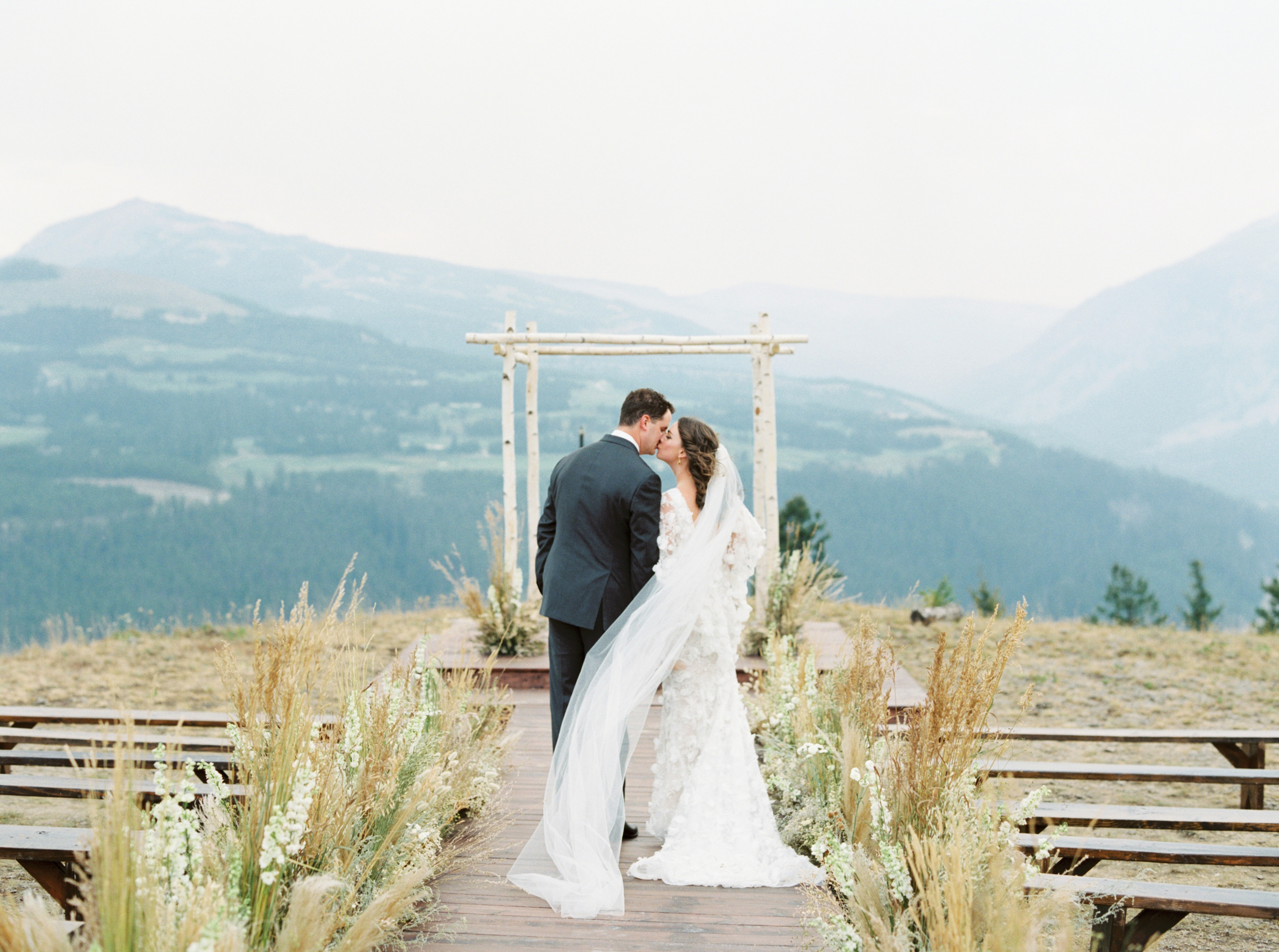 bride and groom standing in wedding aisle kissing