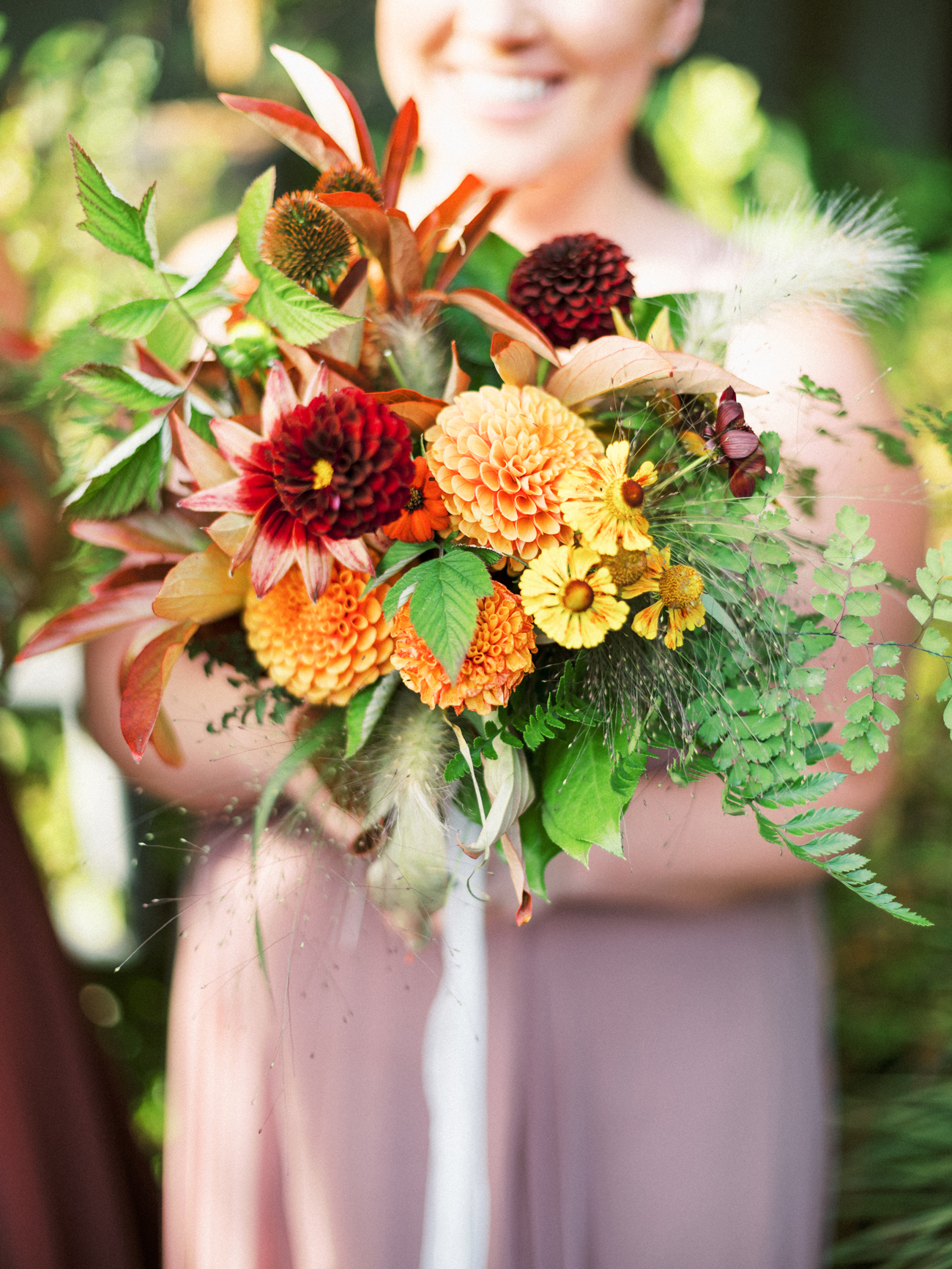 variety of orange and red flowers with greenery bridesmaids bouquets