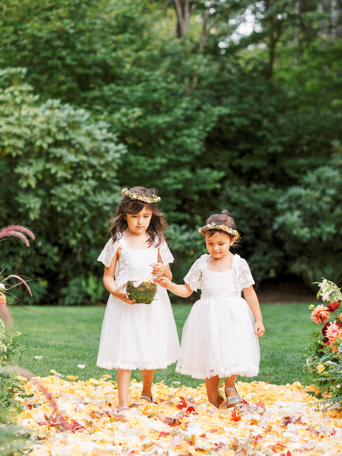 two flower girls wearing white tea length dresses and flower crowns