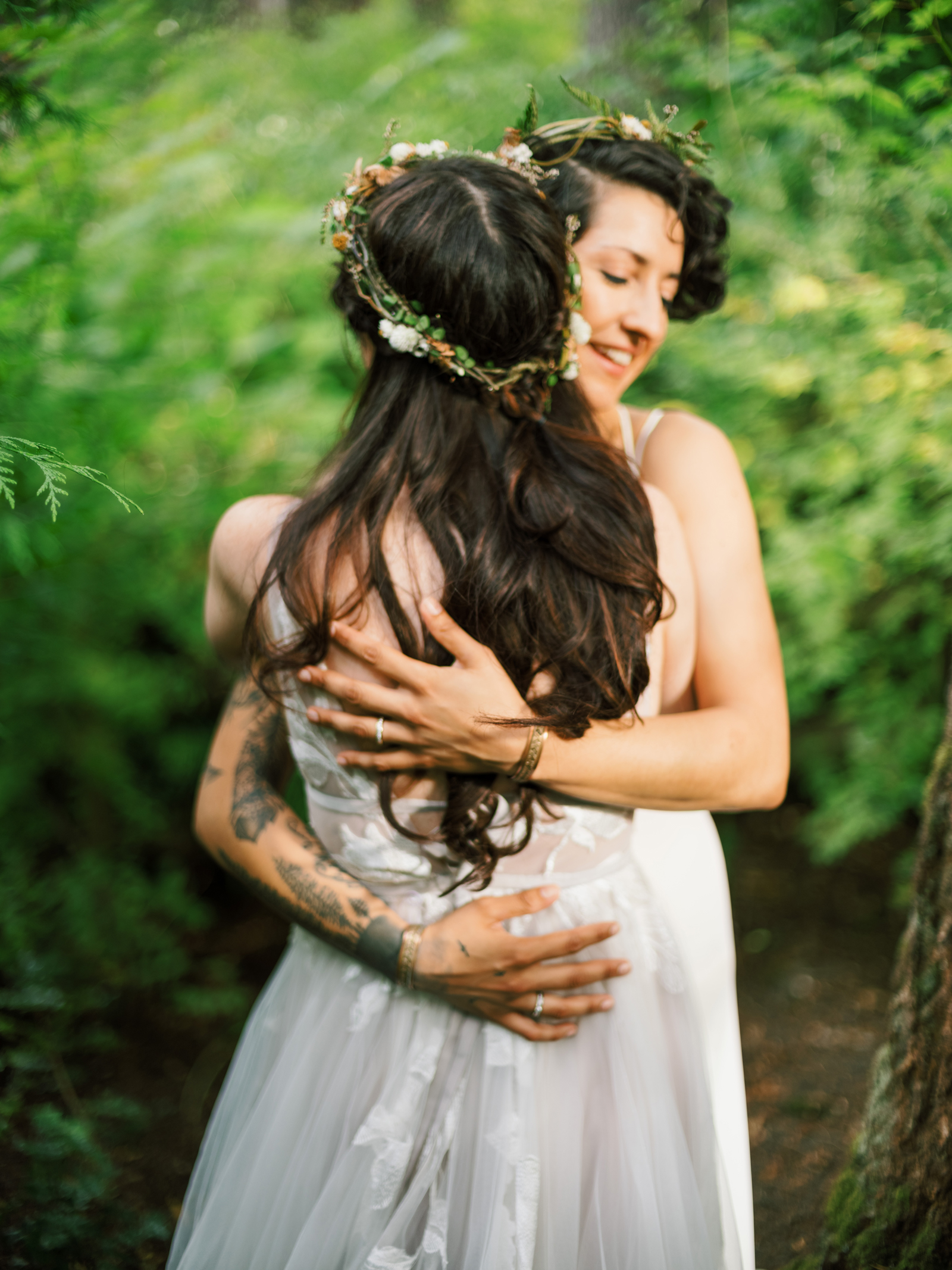 brides hugging during wedding portraits outside in forest