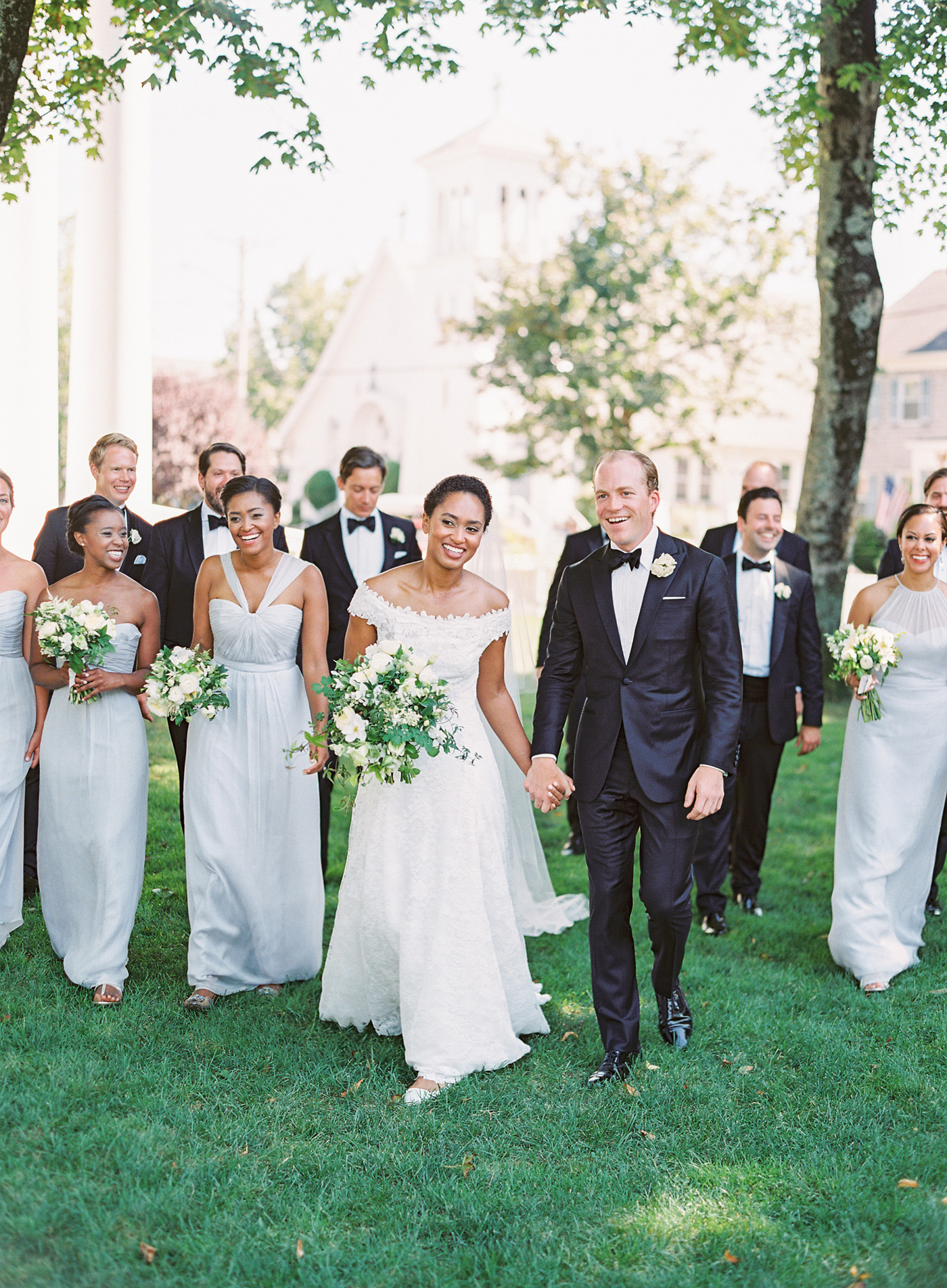 bride and groom with groomsmen wearing black tuxedos and bridesmaids wearing dove-gray chiffon gowns