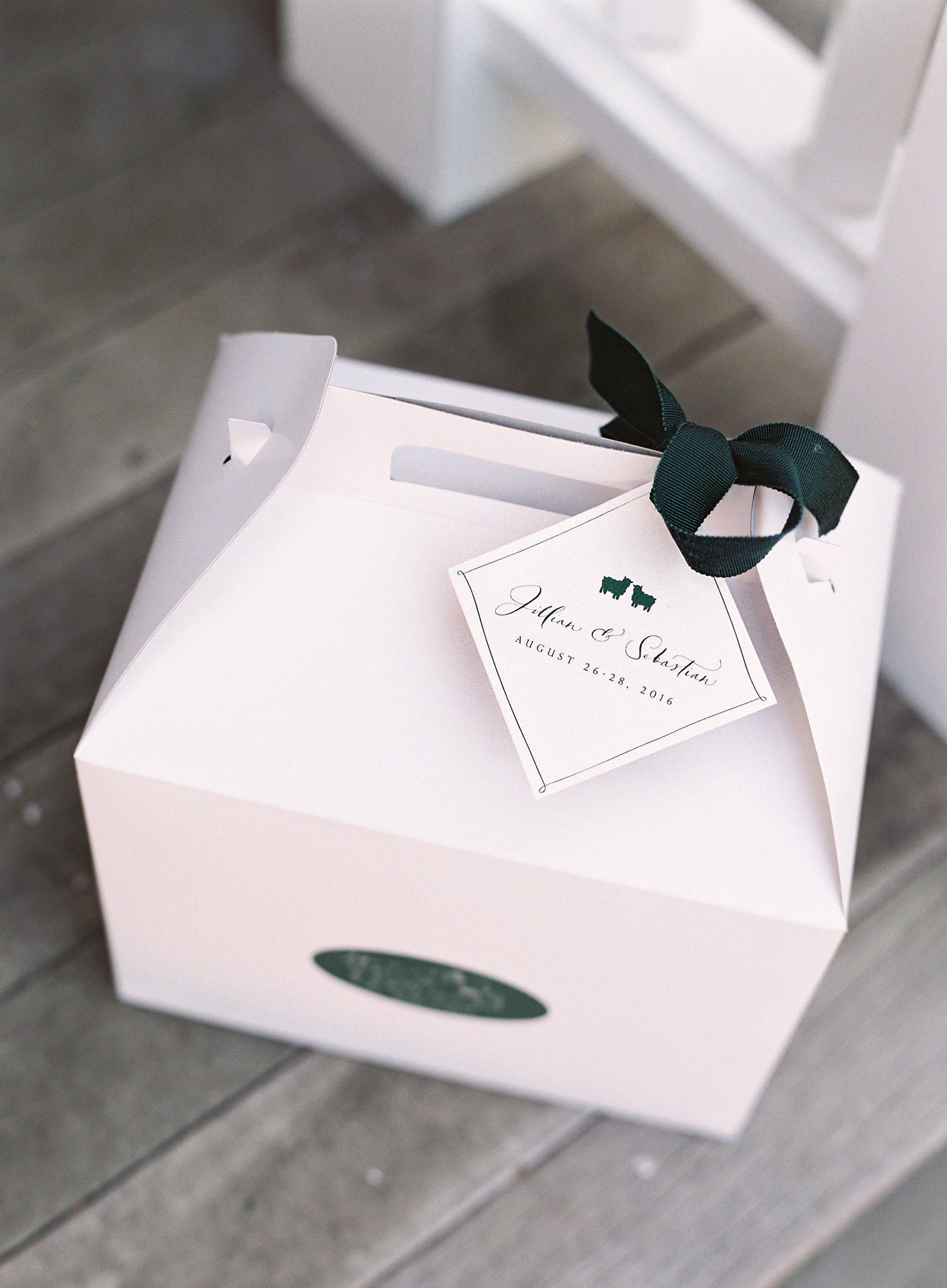 white box with forest green ribbon and tag