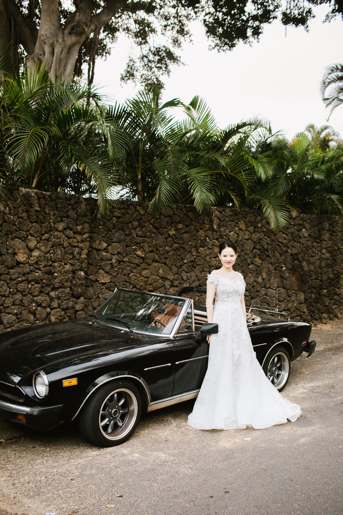 bride standing in front of black convertible car