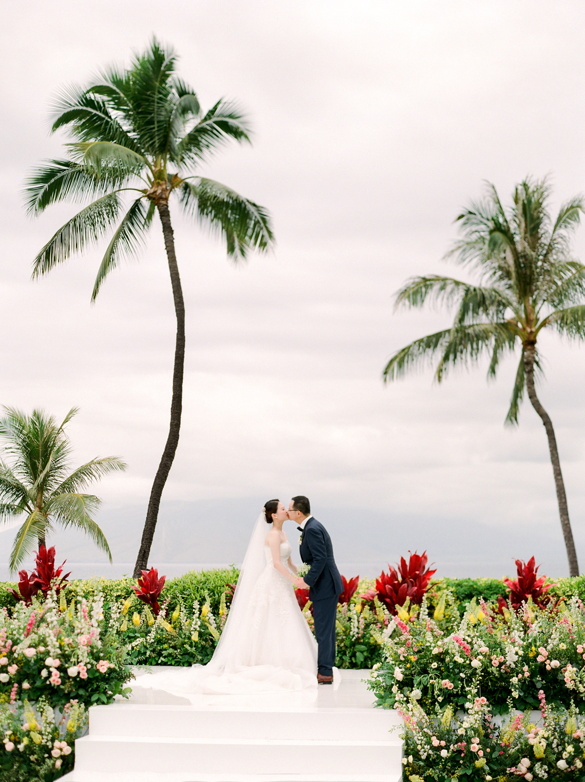 bride and groom kissing on outdoor wedding alter