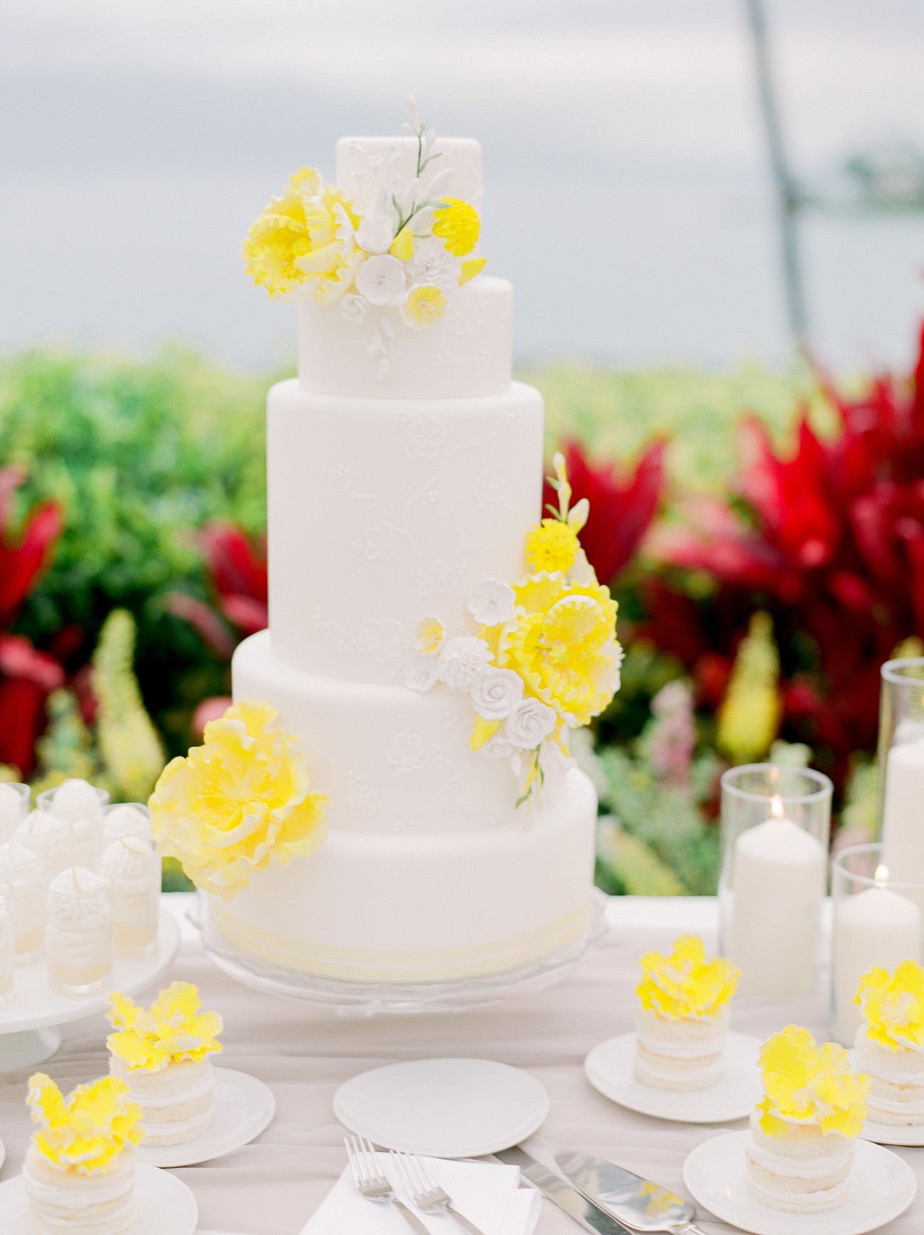 five-tiered white fondant wedding cake with yellow flower decor