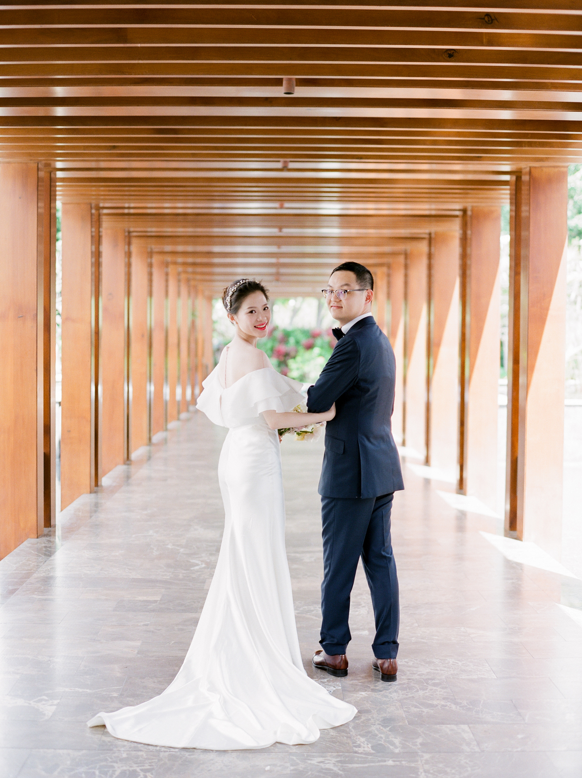bride and groom looking backward under lined archways