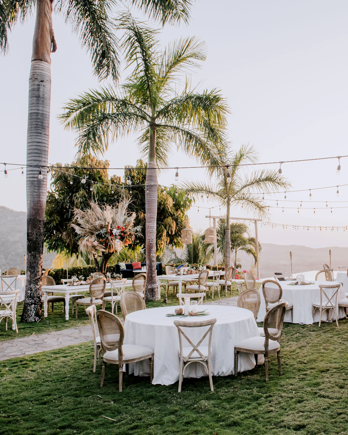 white tablecloth covered reception tables hanging lights