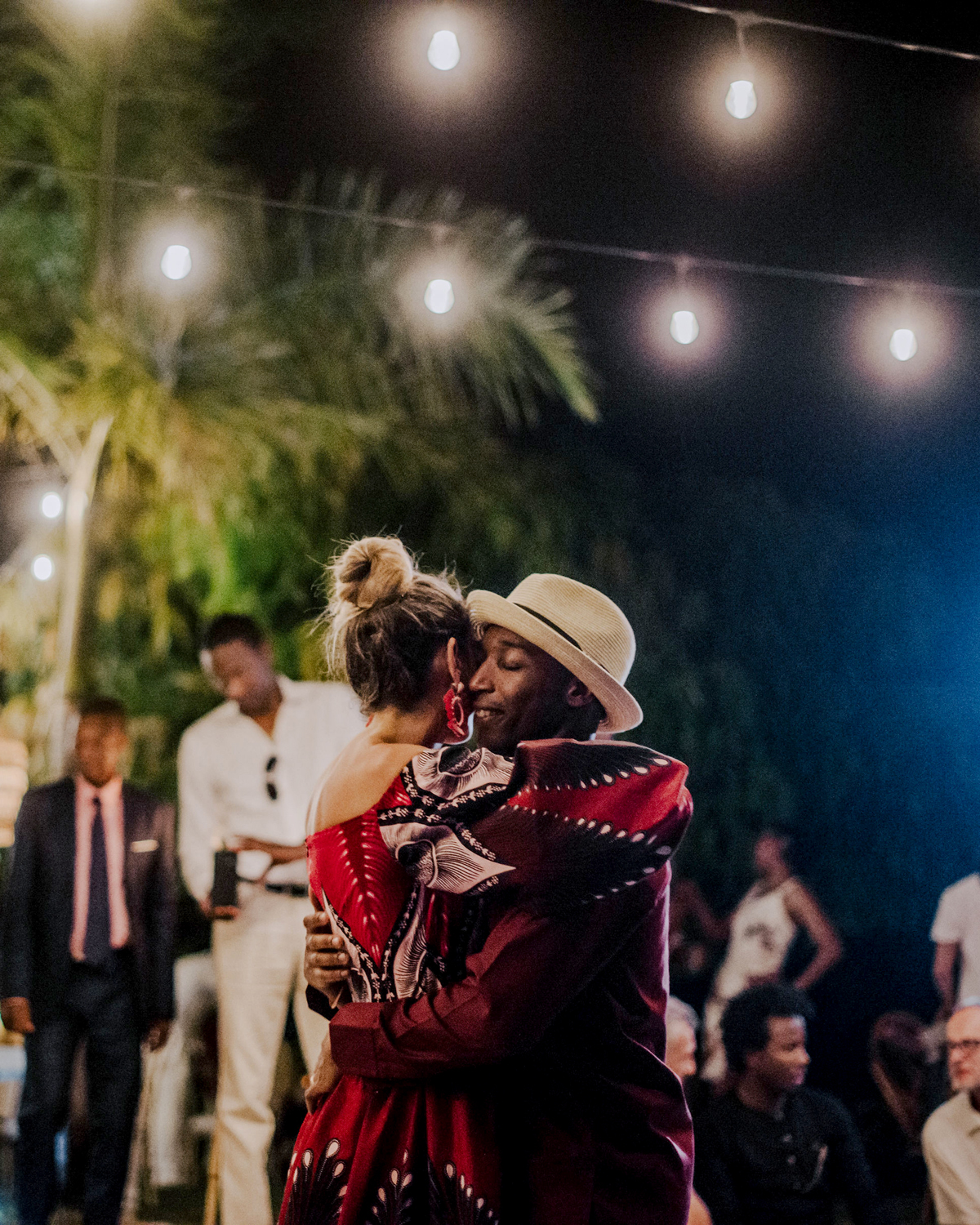 bride and groom wearing matching red outfits during first dance