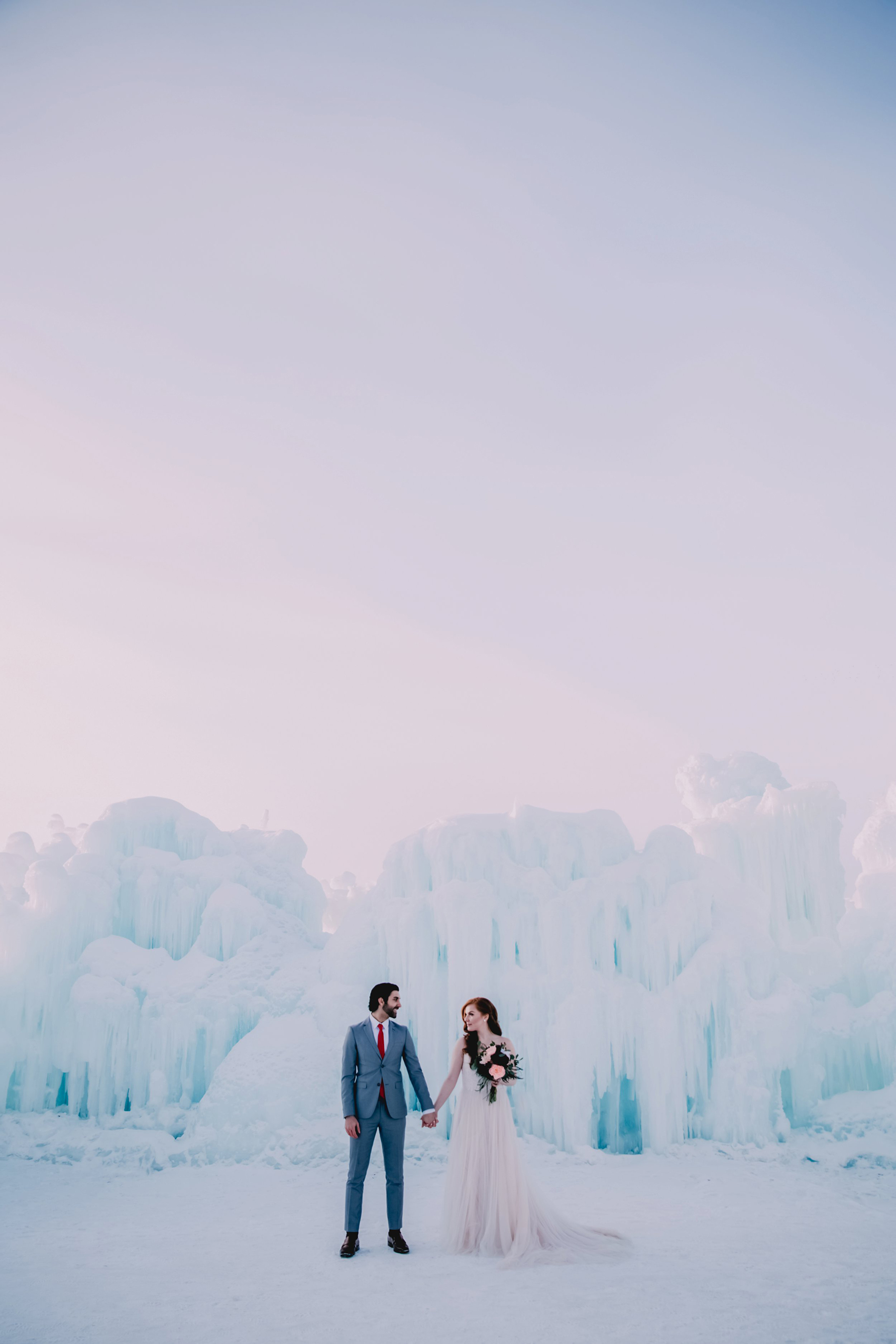 Bride and Groom Posing with Ice Castle
