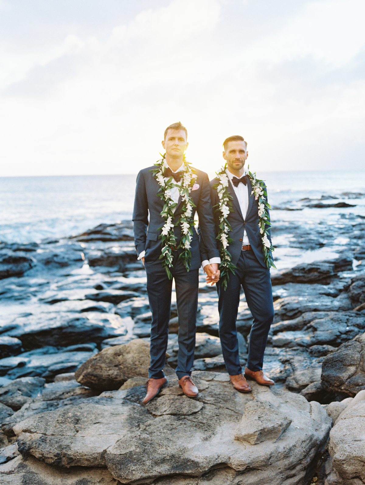 sunset wedding photos grooms holding hands on oceanic rock