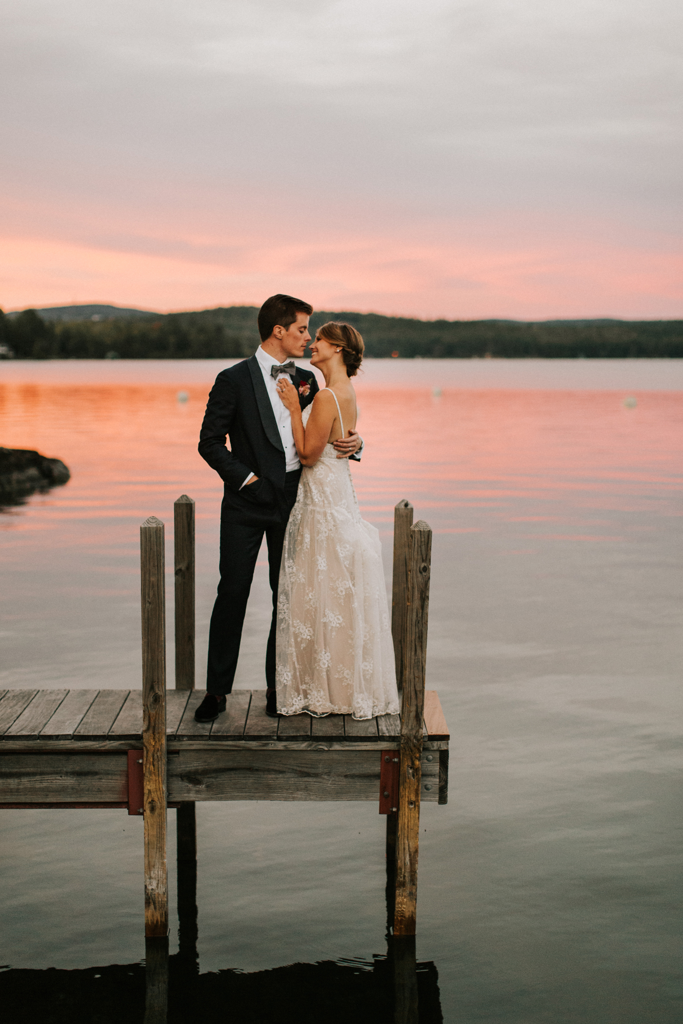 bride and groom standing on the pier at sunset