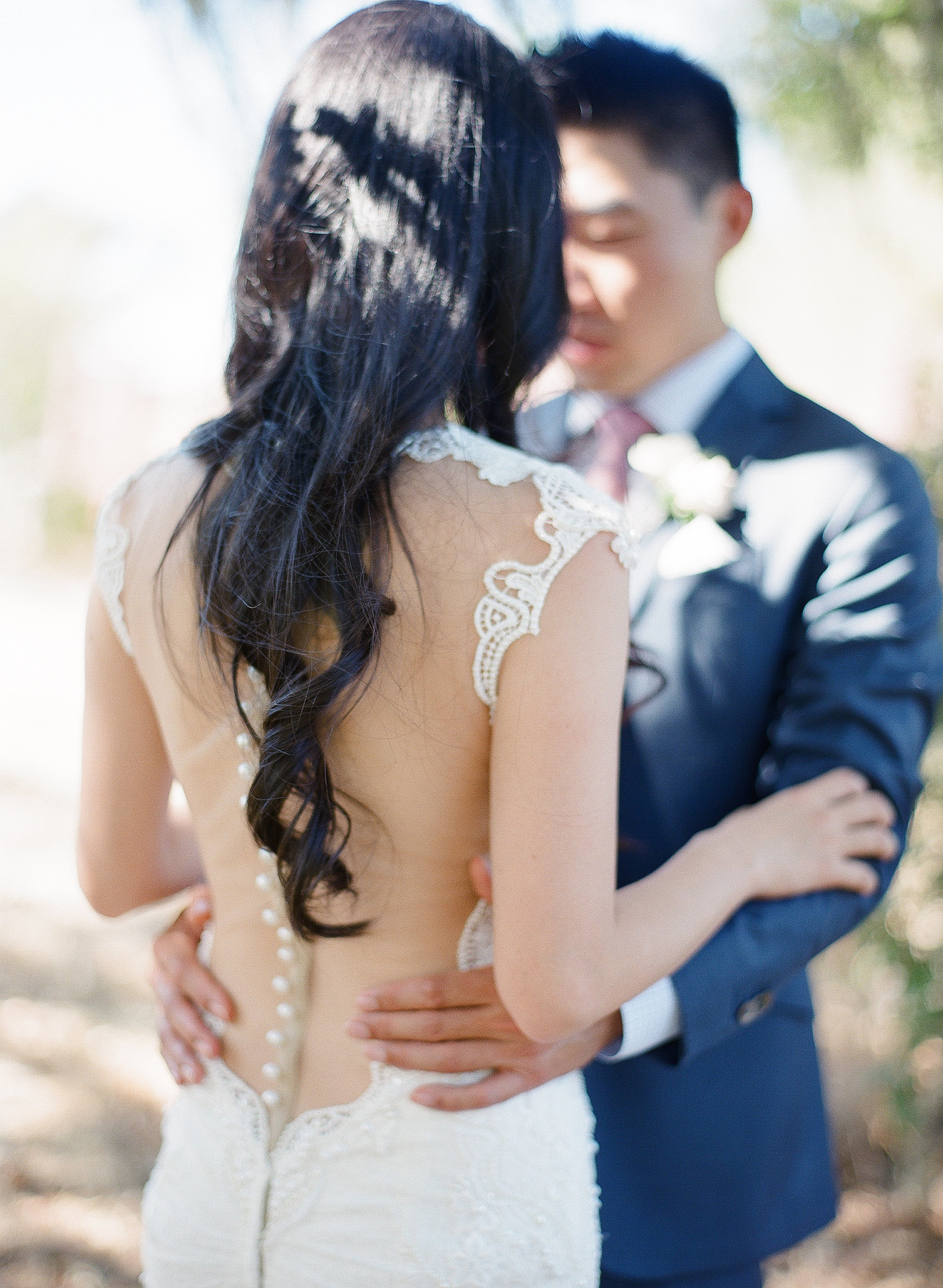 A Bride with an Illusion Back Wedding Dress and Details Down the Spine