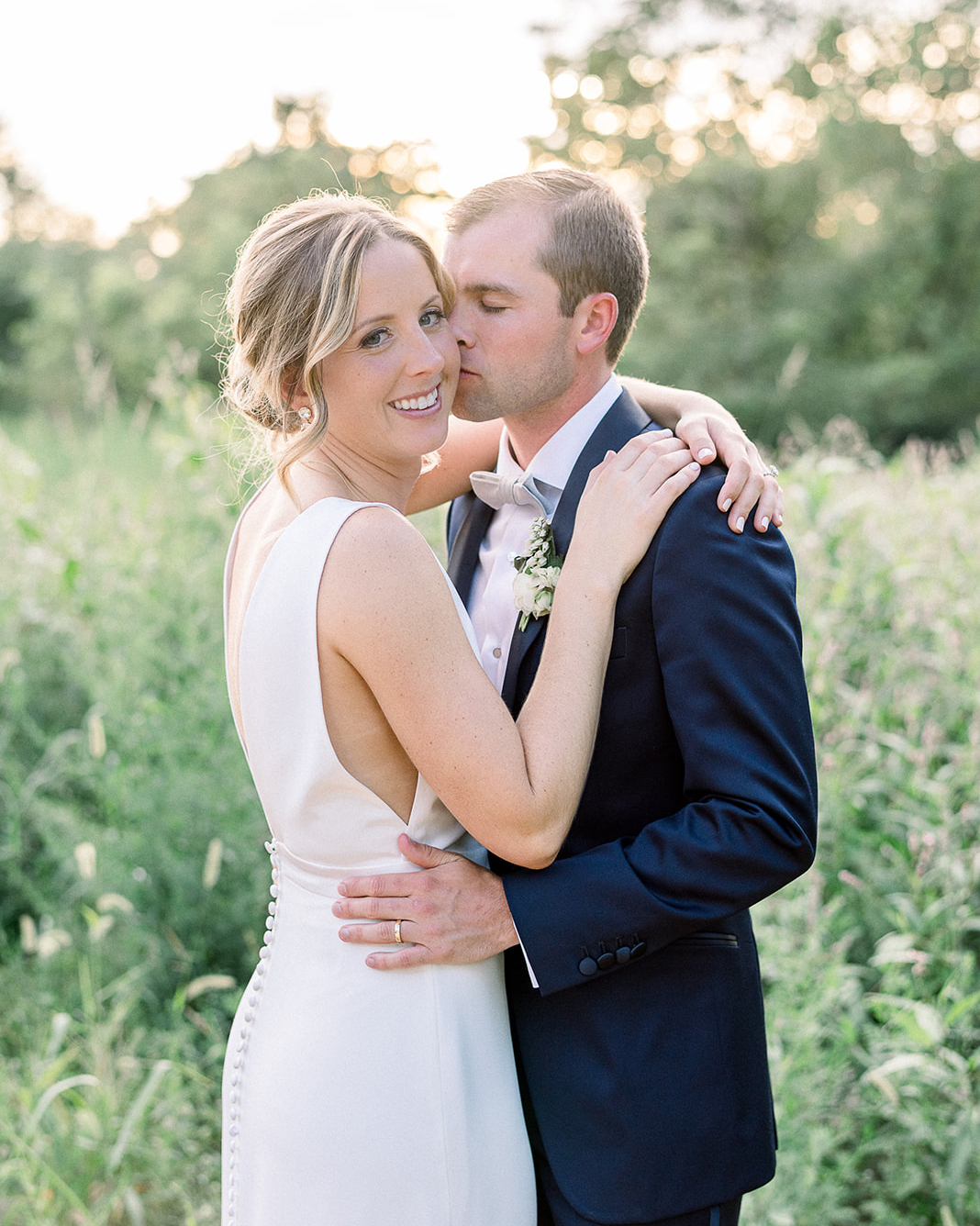 wedding dresses with buttons bride and groom hugging