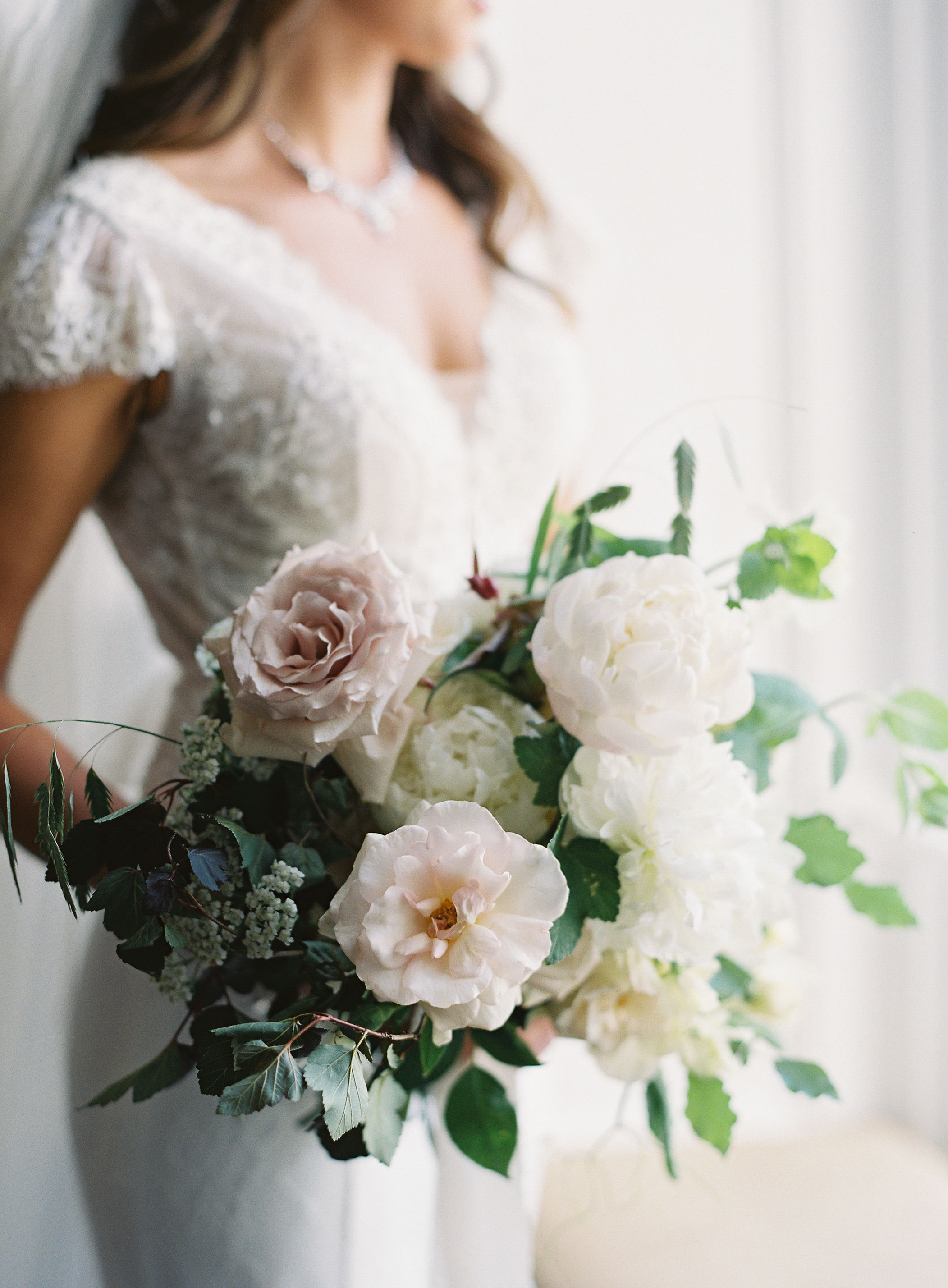 white, cream and very pale blush blooms with dark and light greenery wedding bouquet