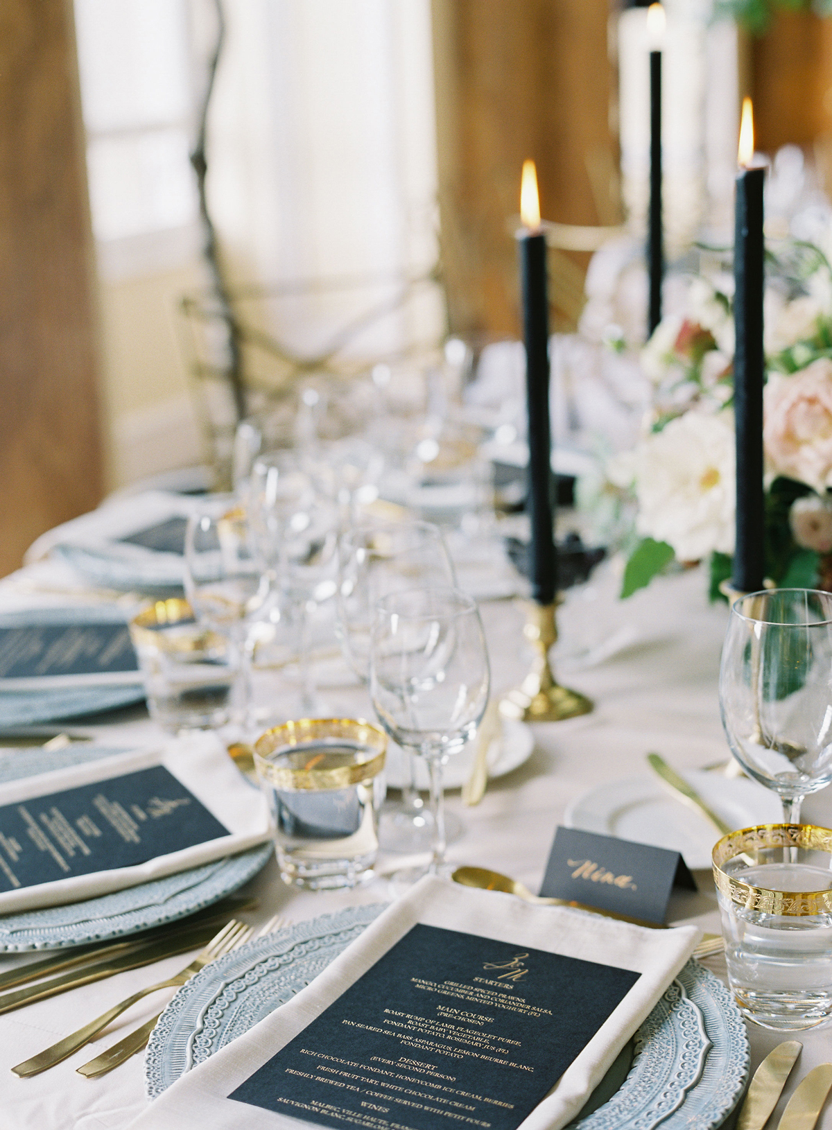 black menus and tall candles on pastel table decor