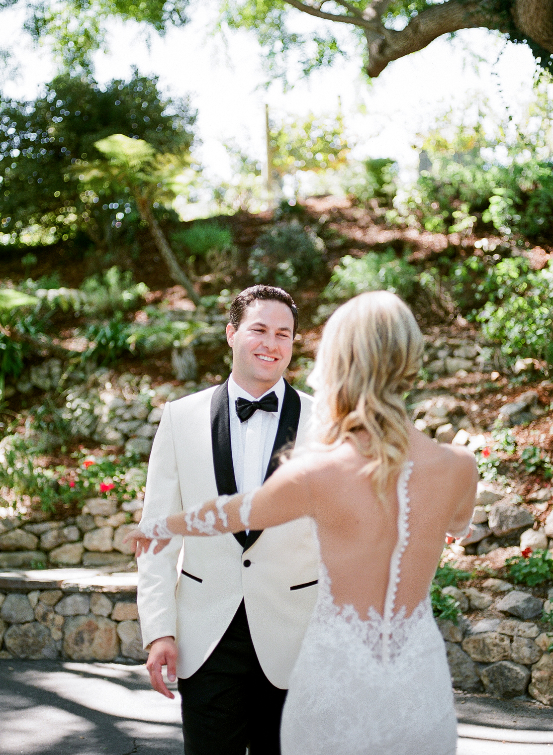 groom smiles at bride during first look
