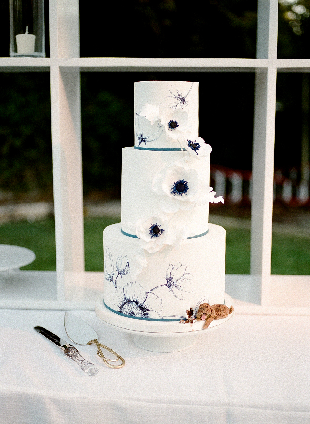 three tiered white frosted cake with custom cosmo flower illustrations
