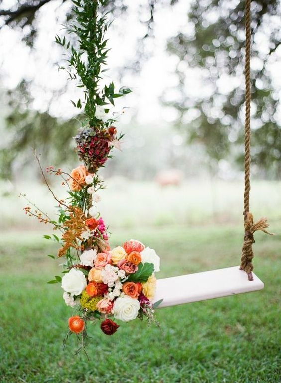 swing decorated with berries, orange, red, and yellow roses along with rusty greenery