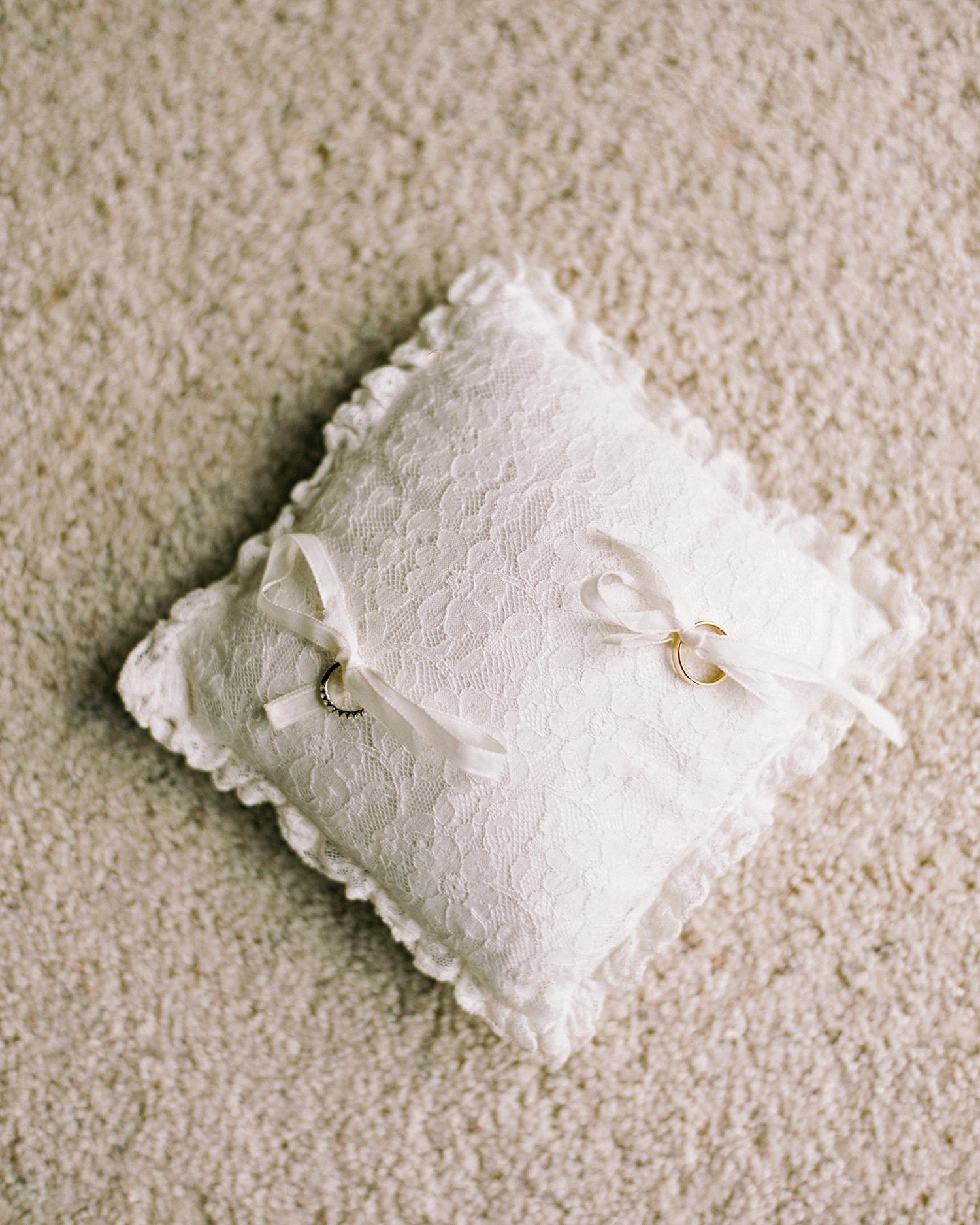 rings tied to white lace pillow