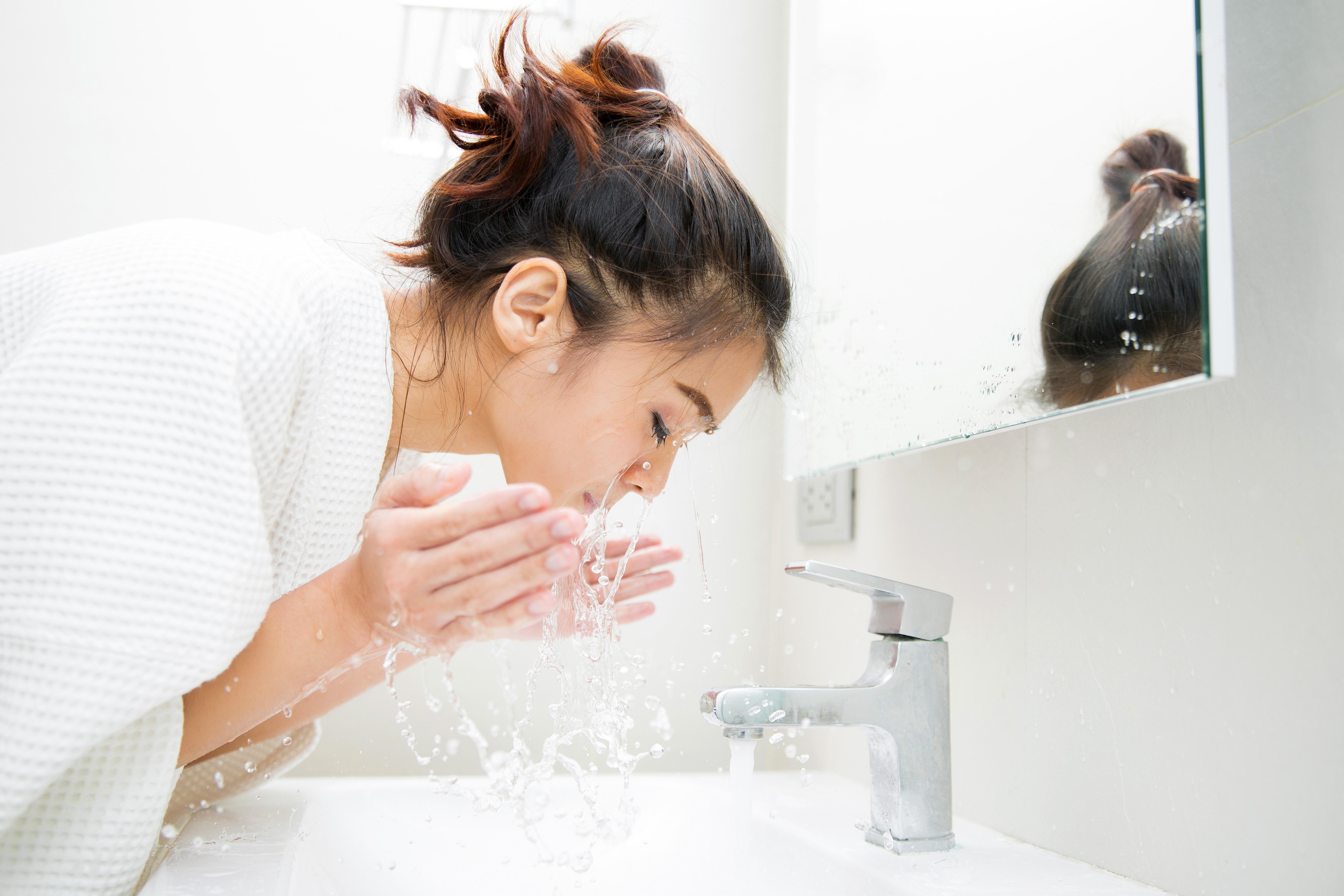 woman splashing water washing face