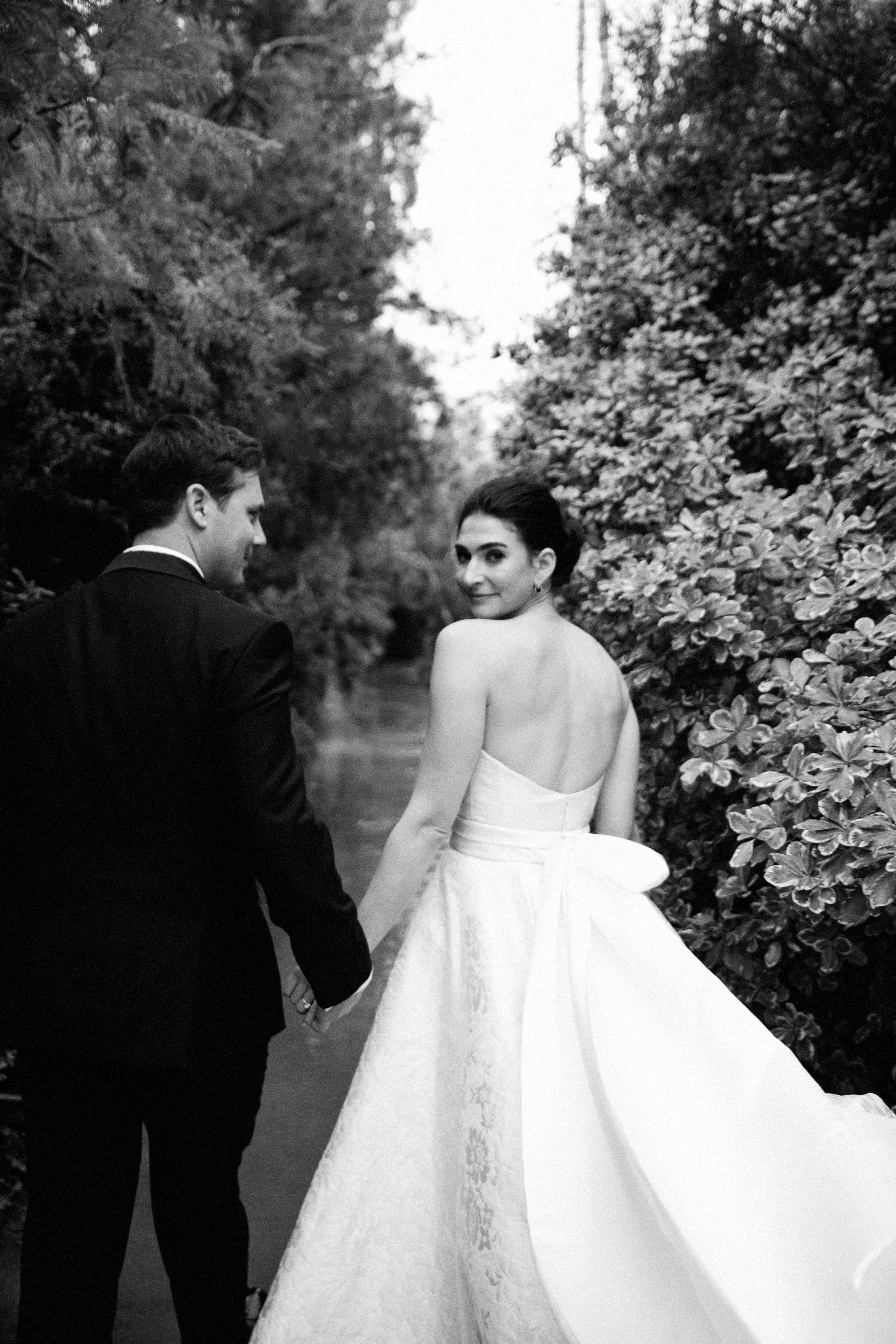 mia patrick wedding couple holding hands while bride looks back