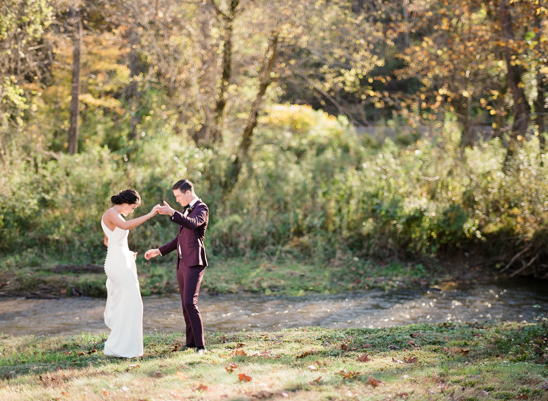 bride and groom share first look outside next to river