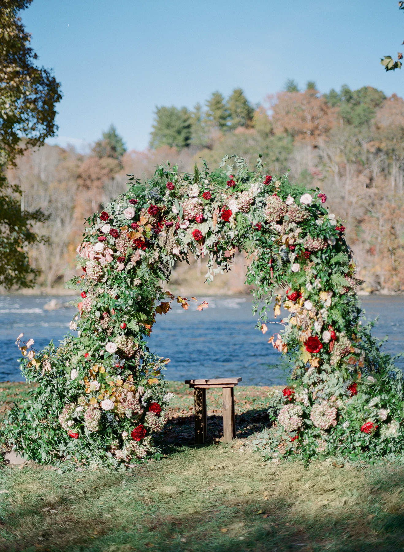 floral arch wedding ceremony backdrop next to river