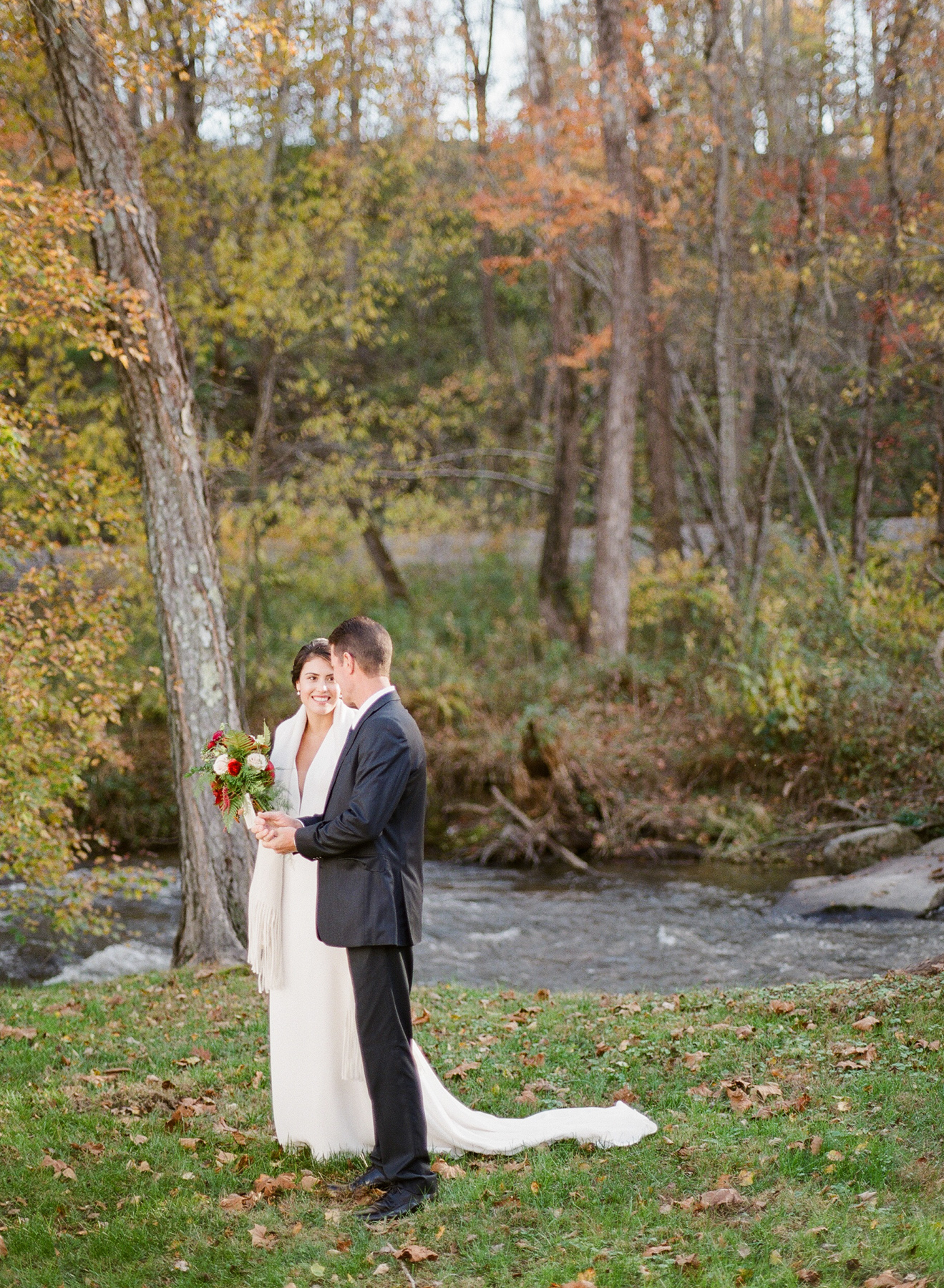 bride and groom standing next to river surrounded by trees