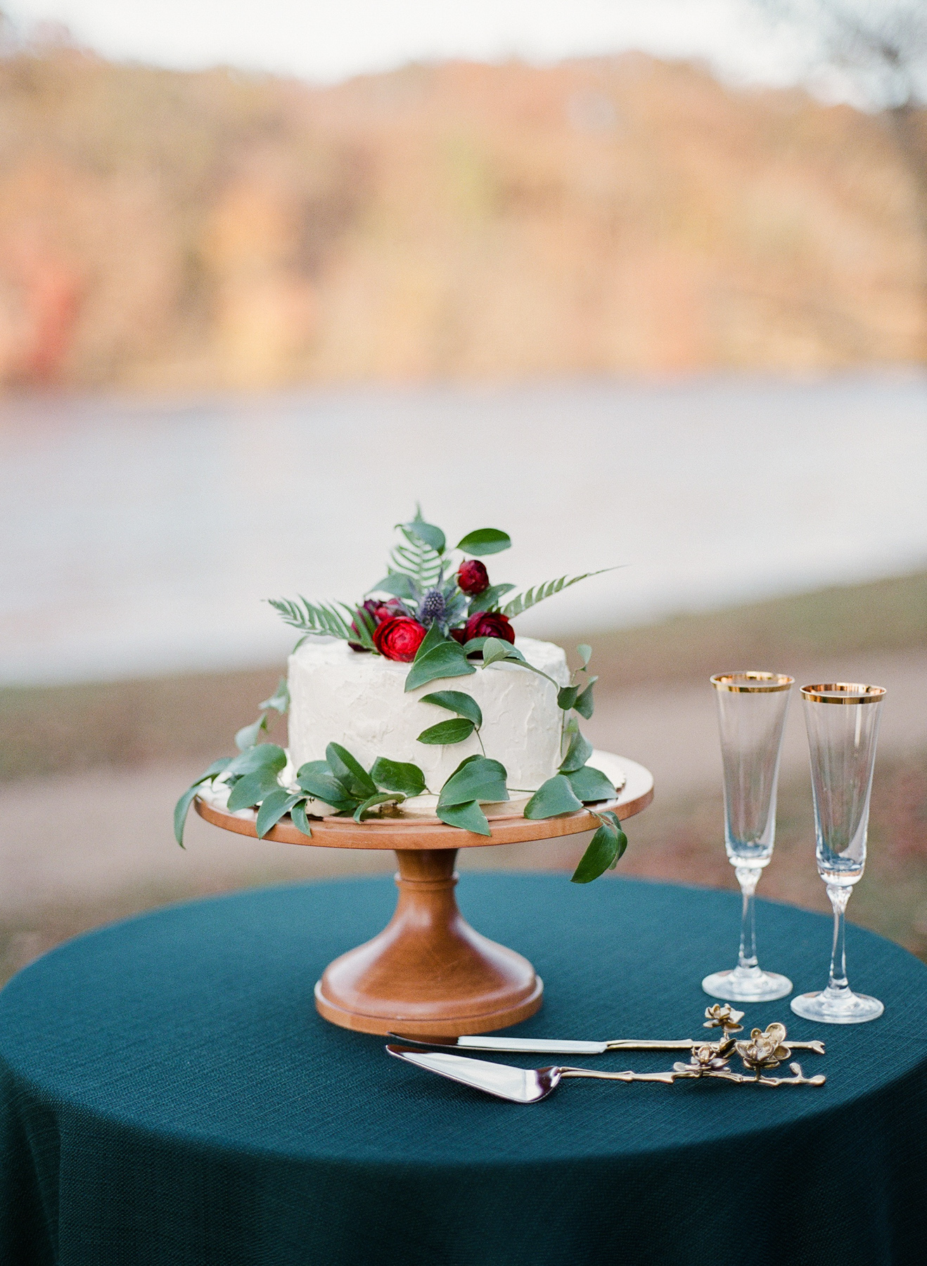 small white frosted single-tier vanilla wedding cake with greenery