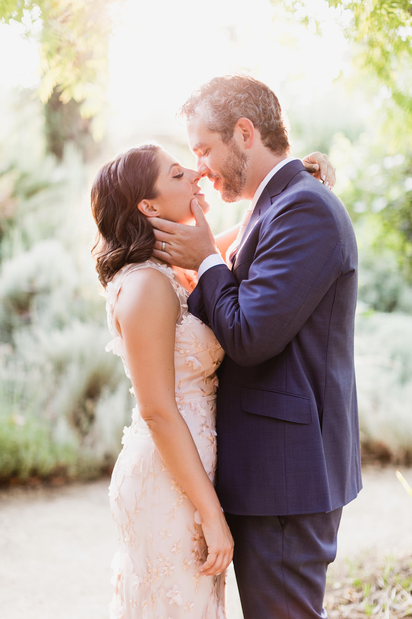 bride and groom stand on garden pathway in sunlight