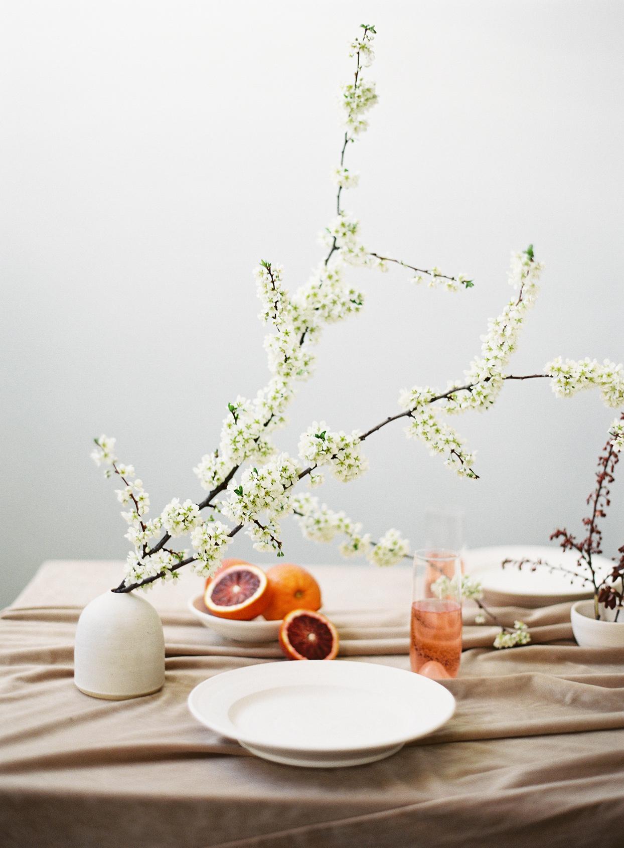 minimalist ikebana short vase with tall flowers on table with oranges