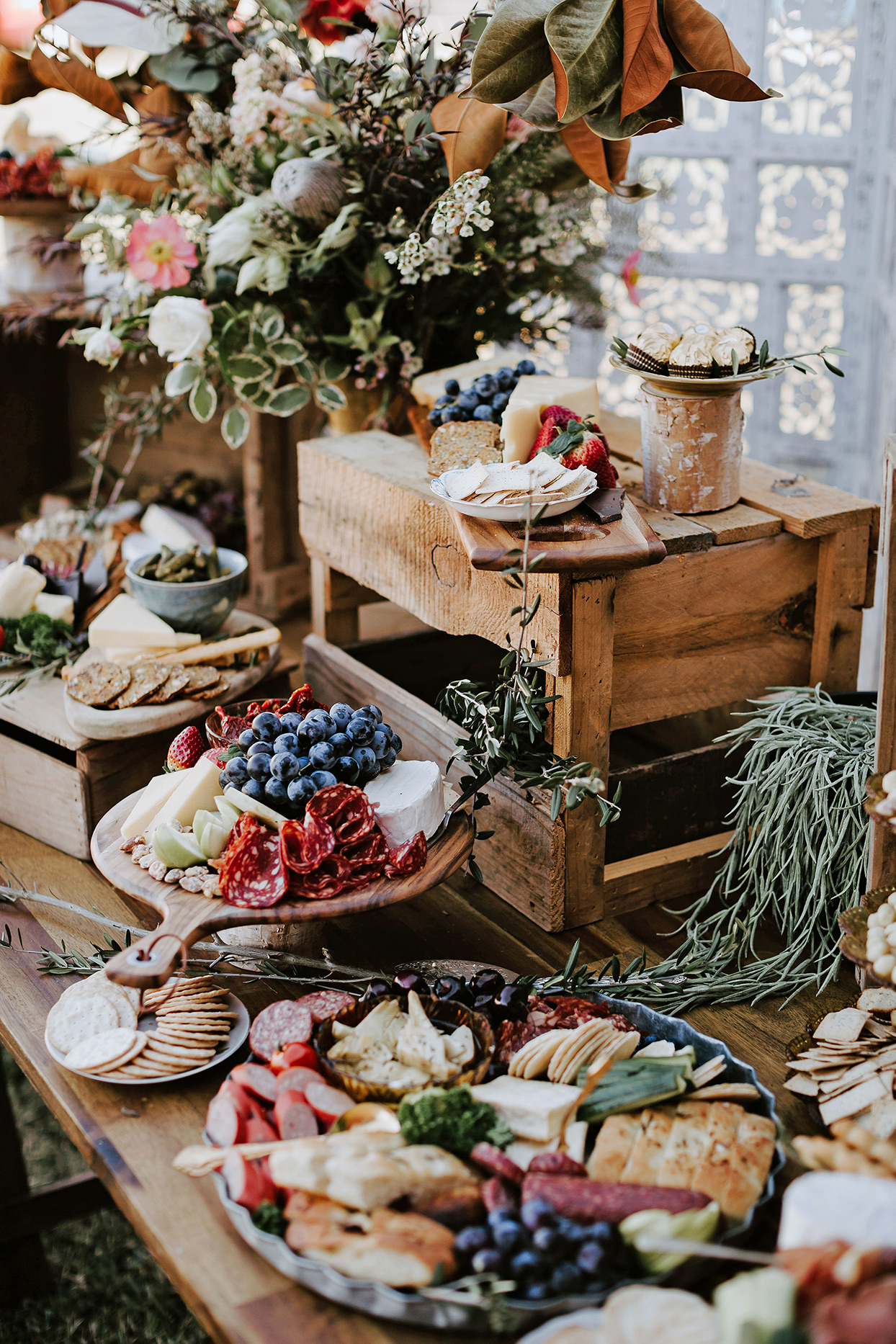 wedding grazing table with wooden risers and platters of food