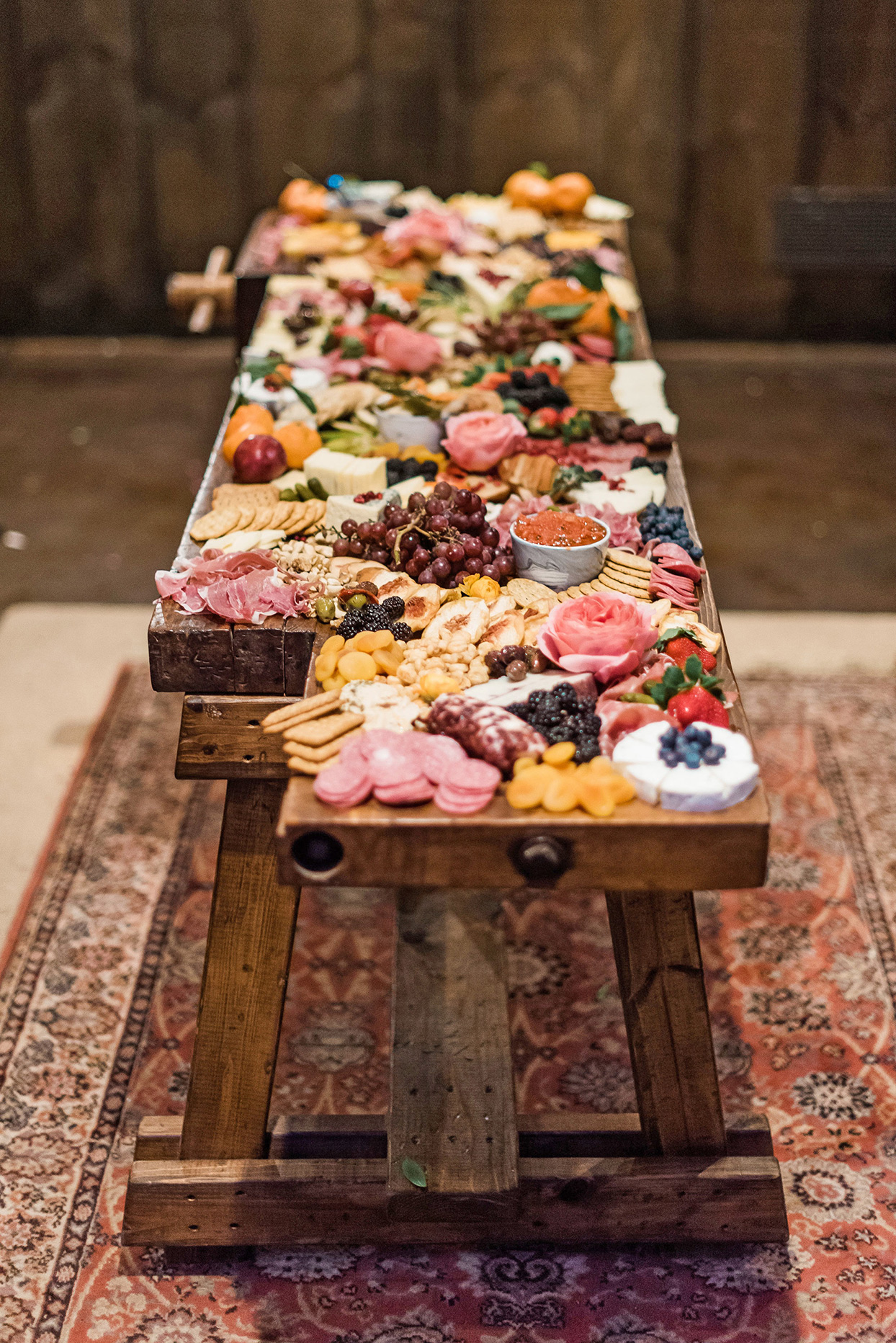 wooden wedding grazing table filled with food