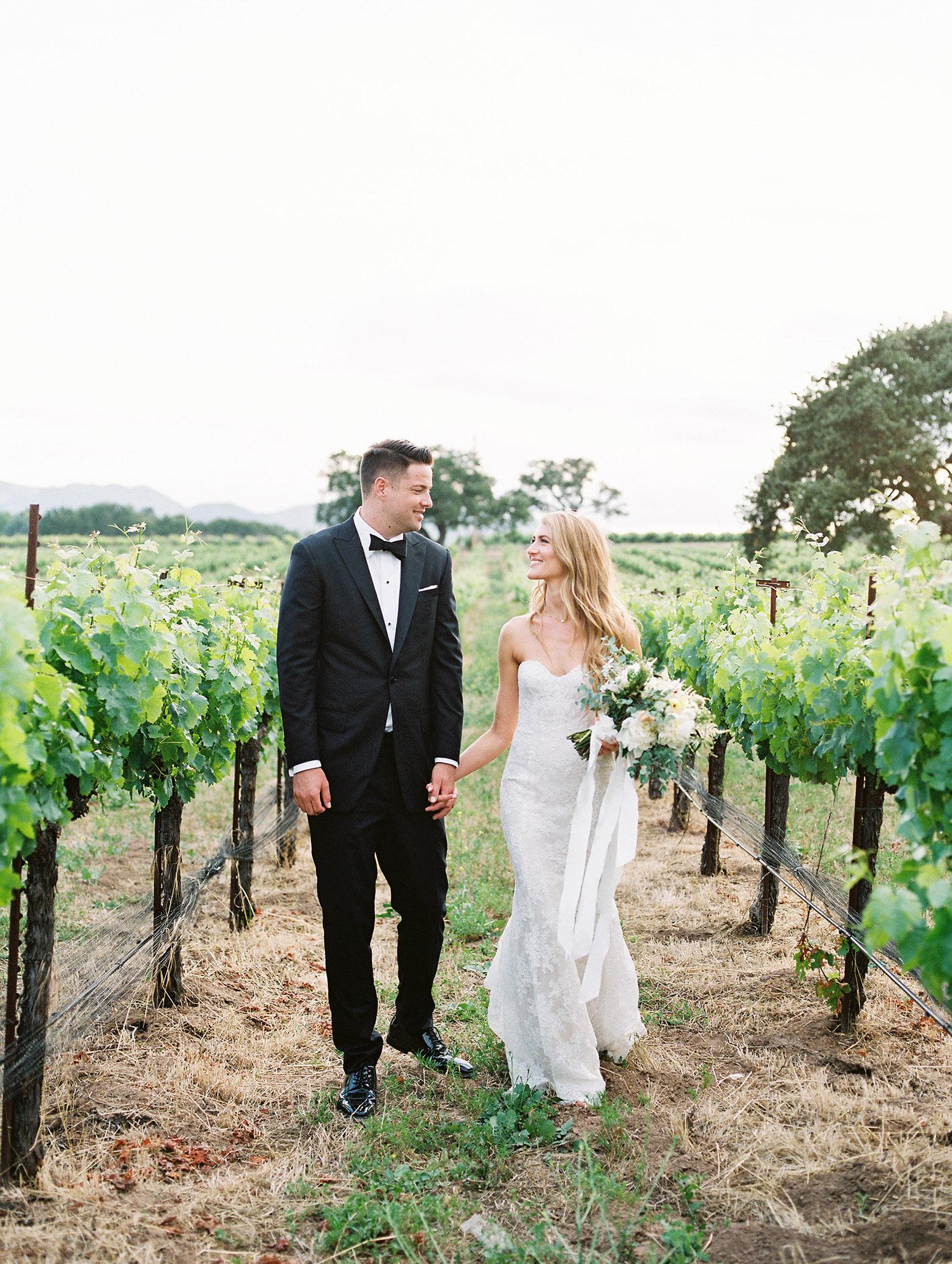 kati erik wedding couple holding hands in vineyard
