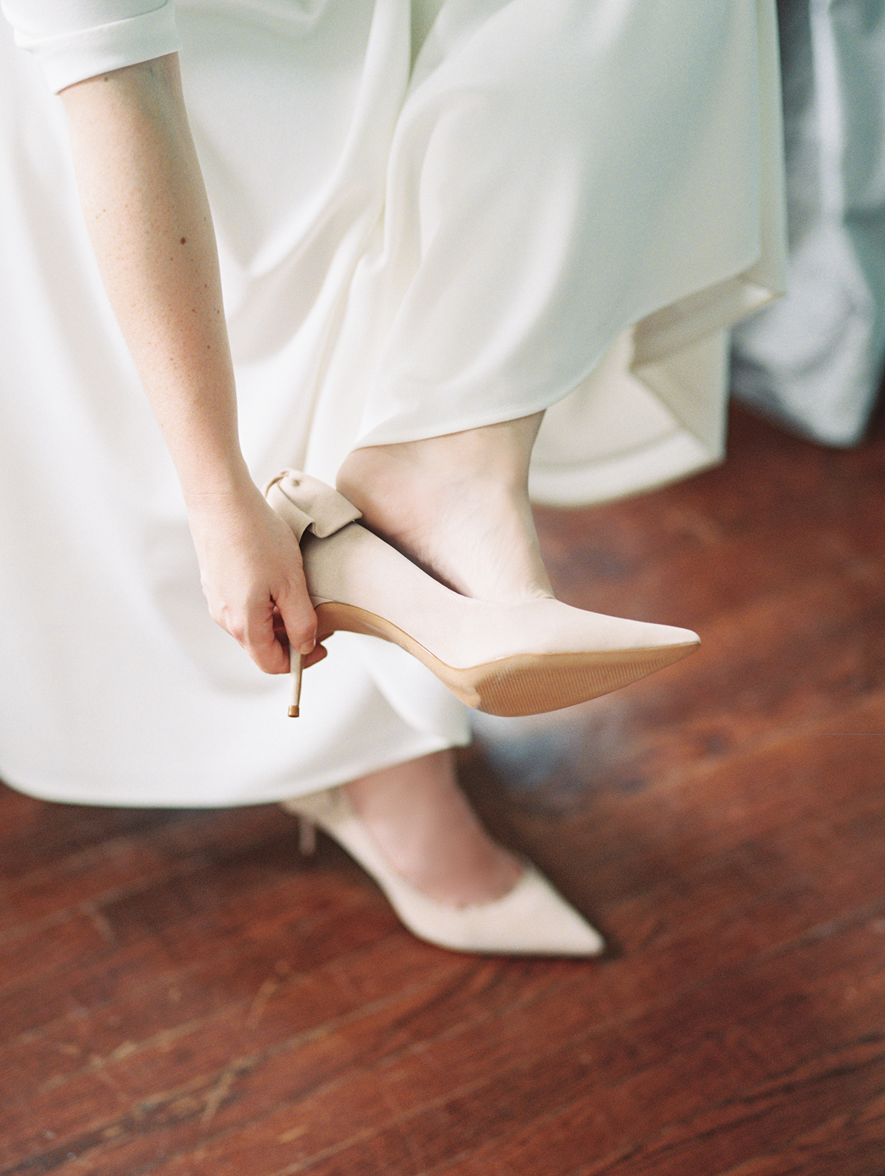 elizabeth scott bride putting on wedding shoes