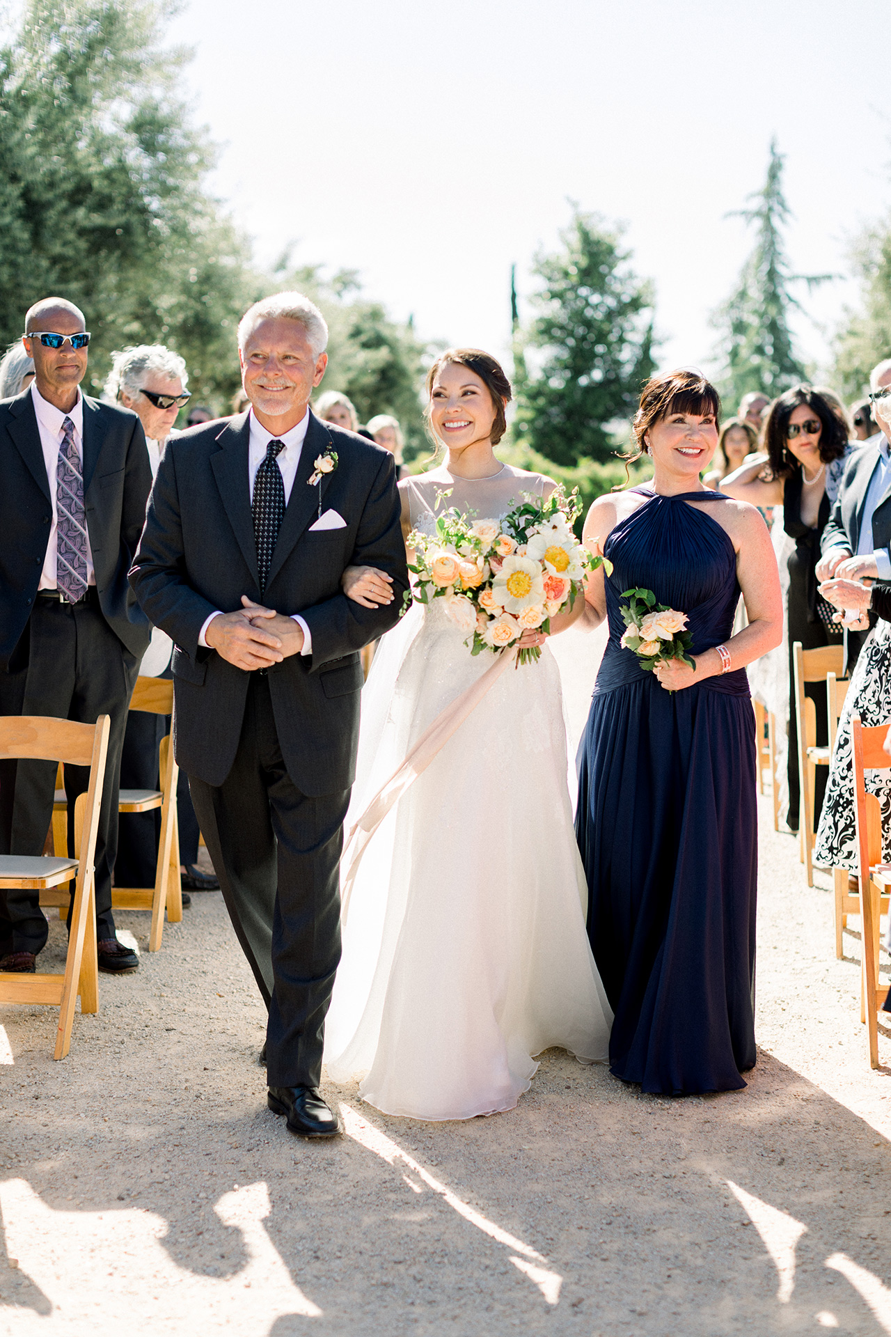 bride parents walk down aisle outdoors