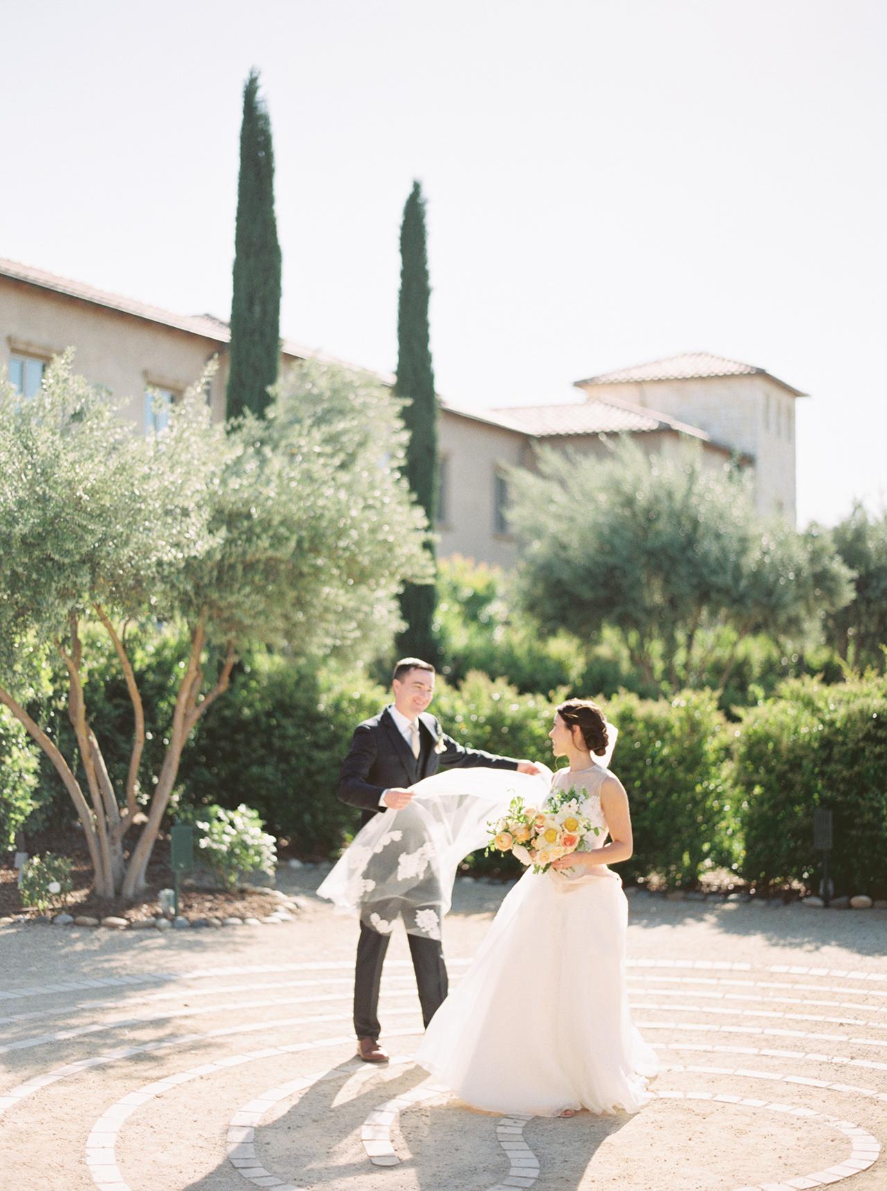groom holding brides veil outdoors vineyard