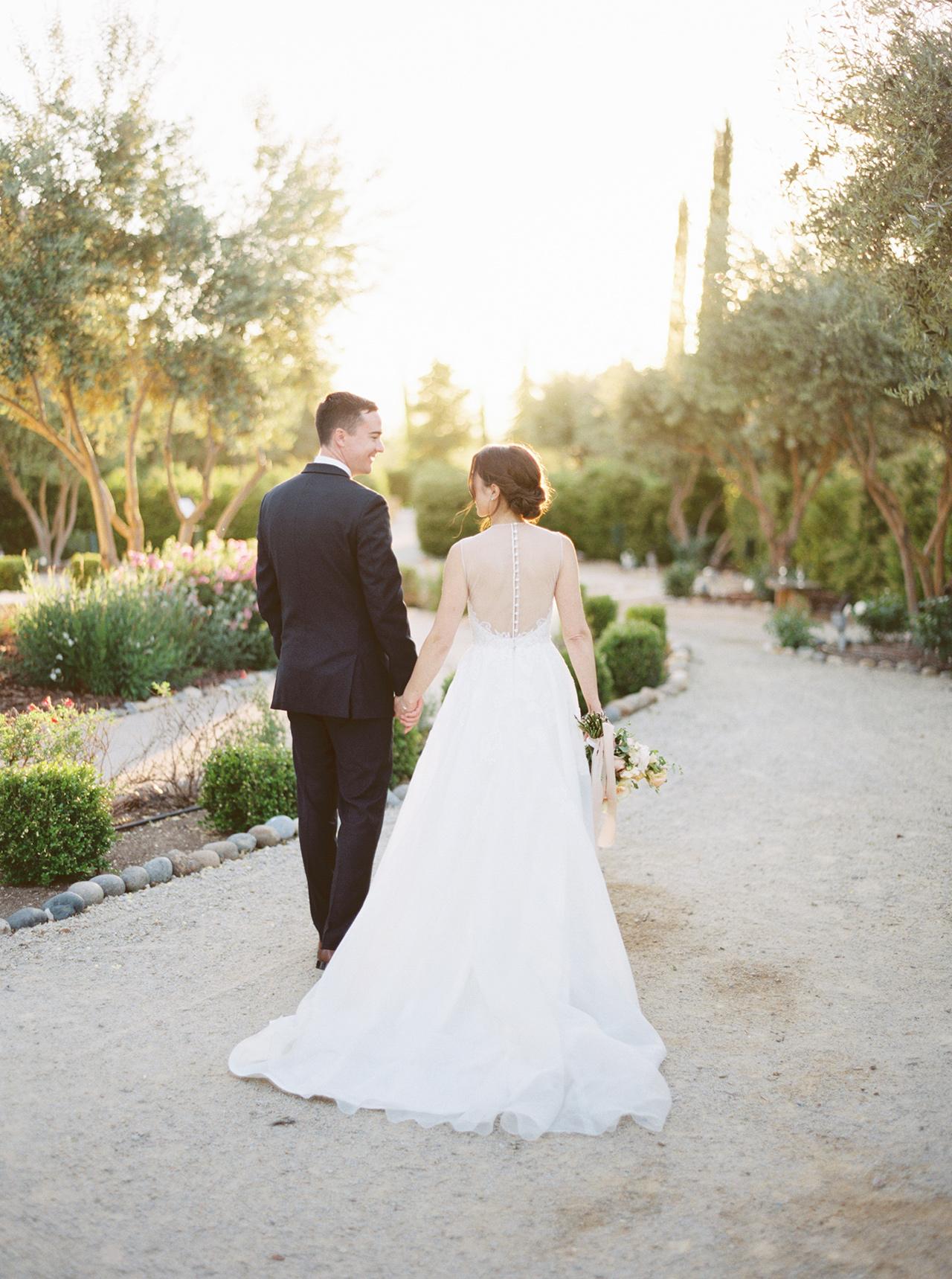 wedding couple walking along garden path