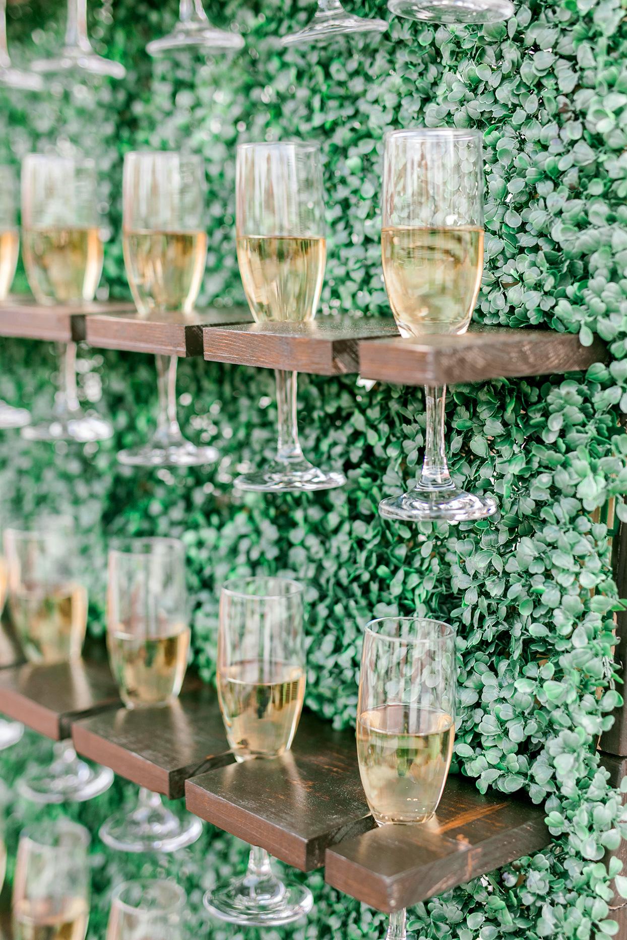 champagne wedding ideas glasses mounted on foliage