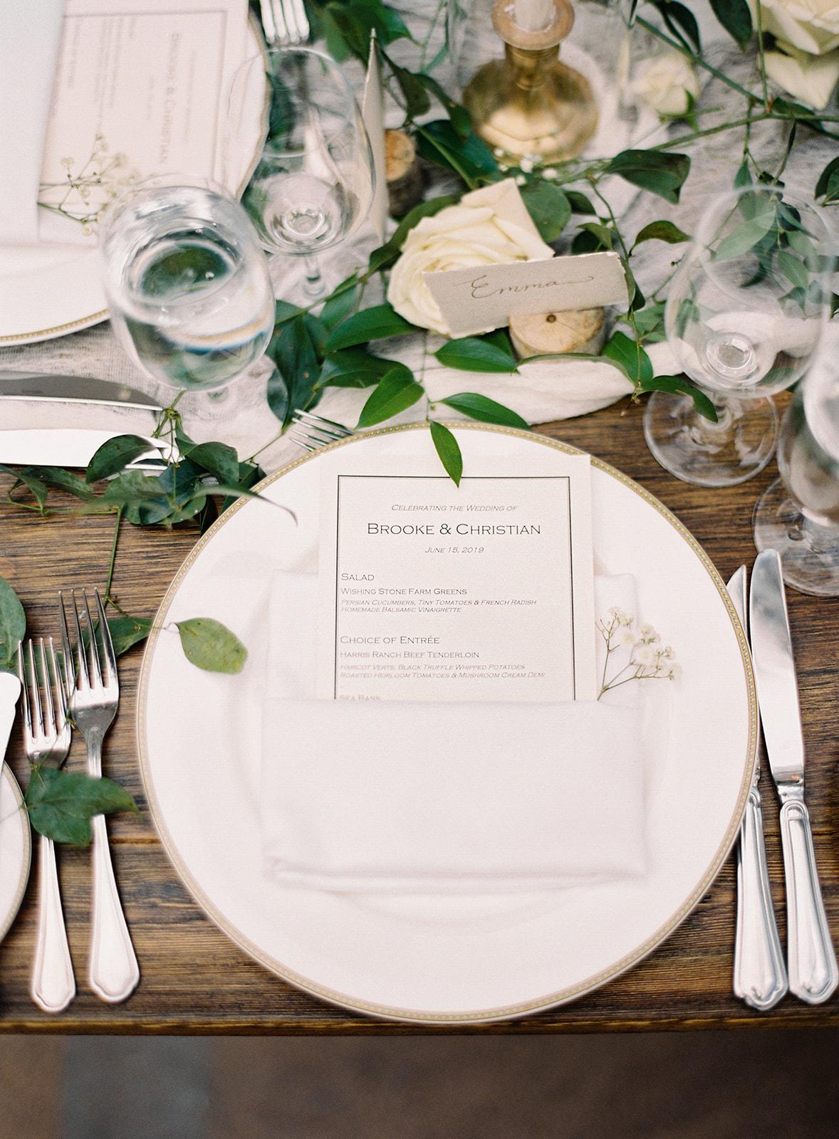 wedding reception wooden tables place setting floral arrangement menu