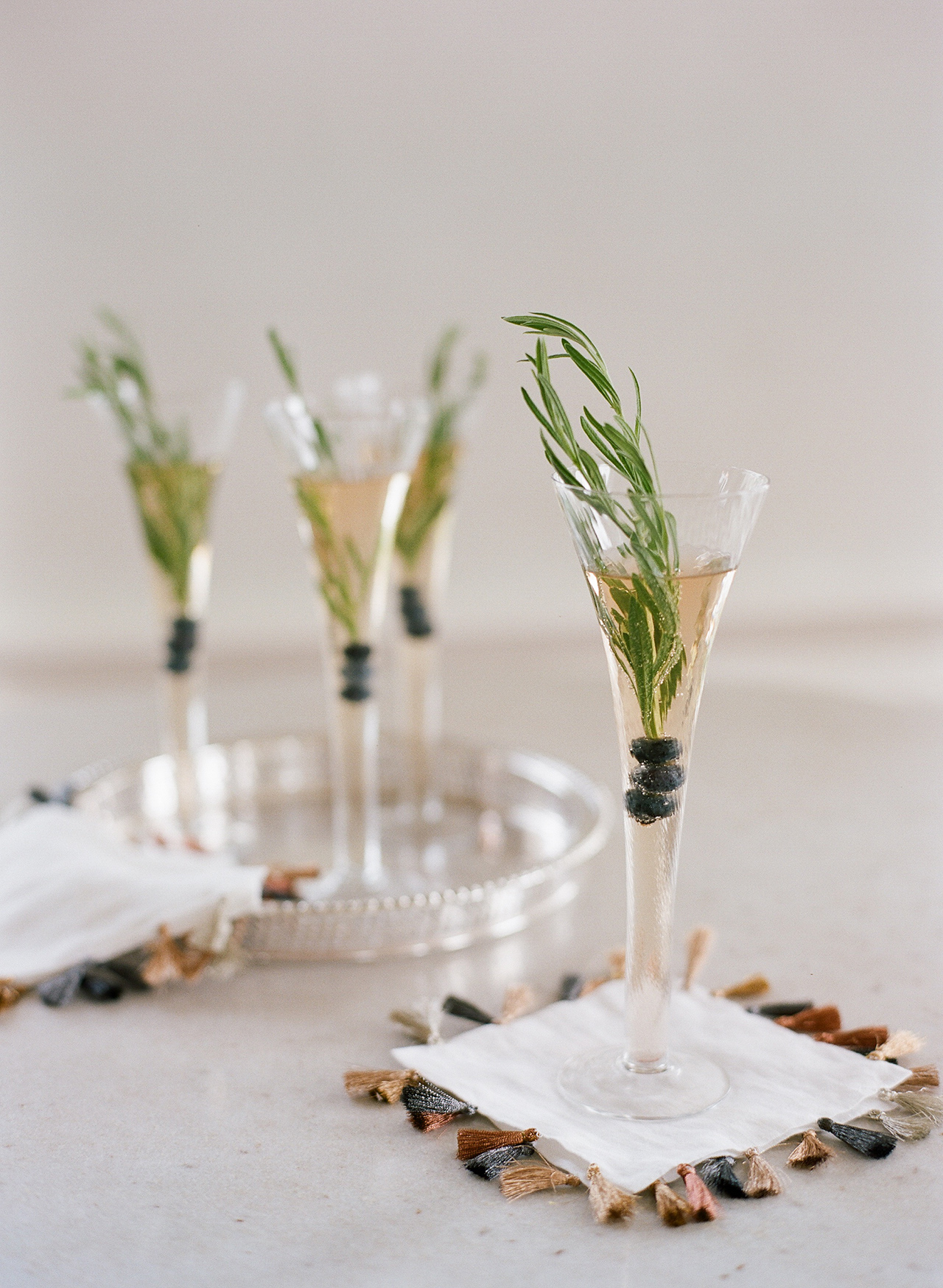 bubbly beverage with rosemary sprigs and blueberries