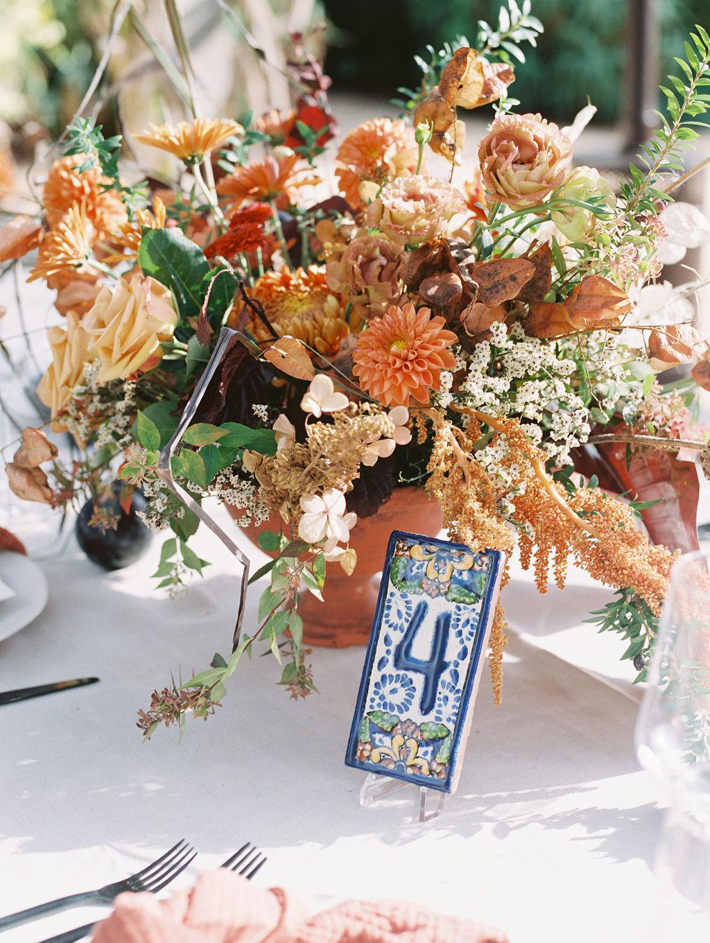 dahlias rust astilbe roses fall floral arrangement blue tile table number