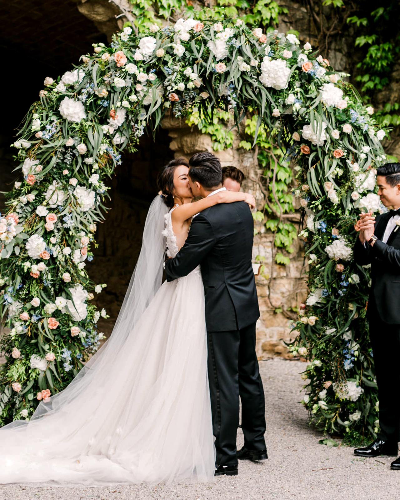 wedding reception kiss under floral arch