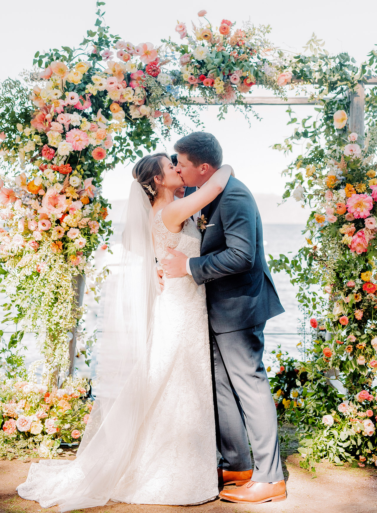 bride groom wedding kiss lake view under arch
