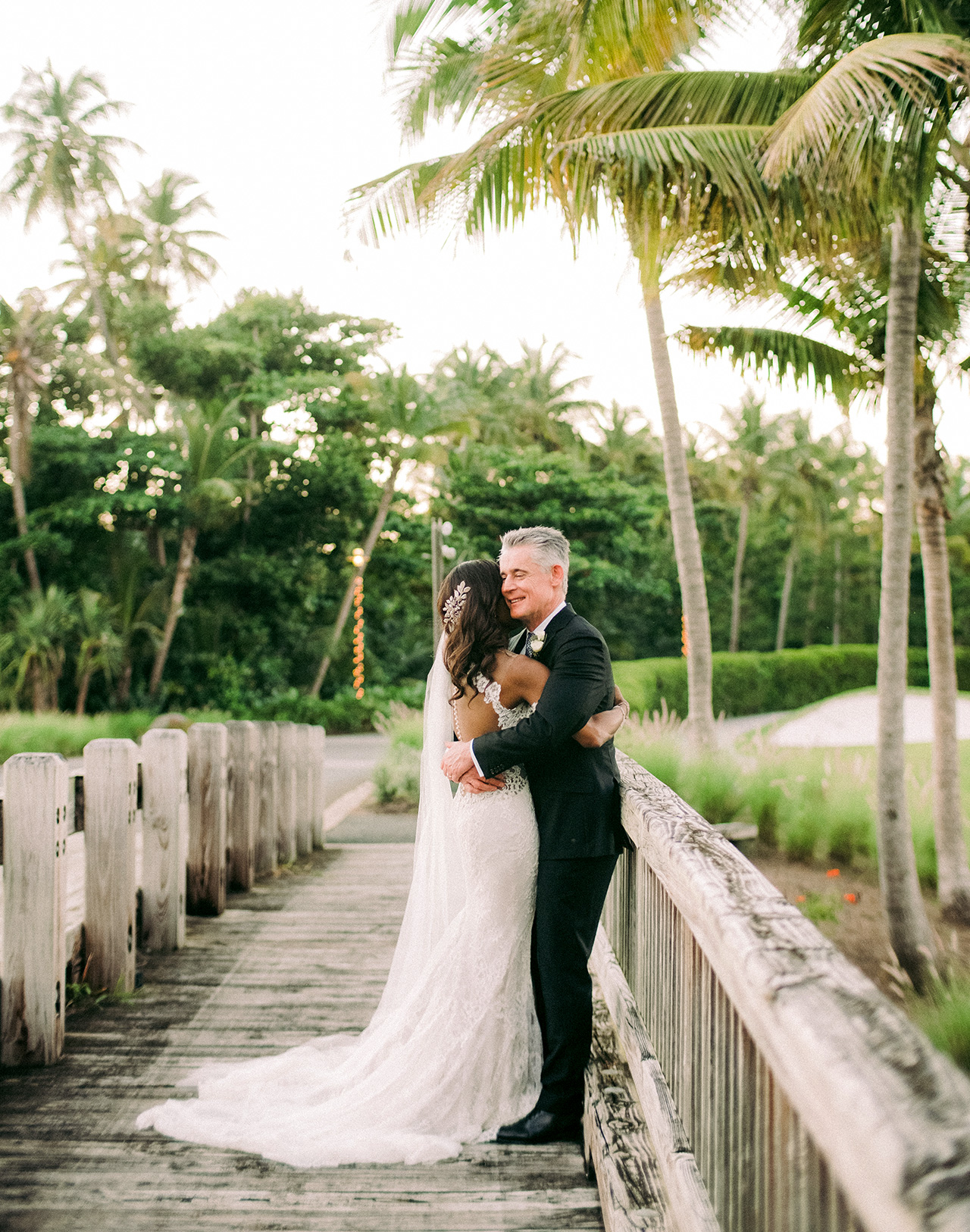 bride groom hold each other on wood bridge