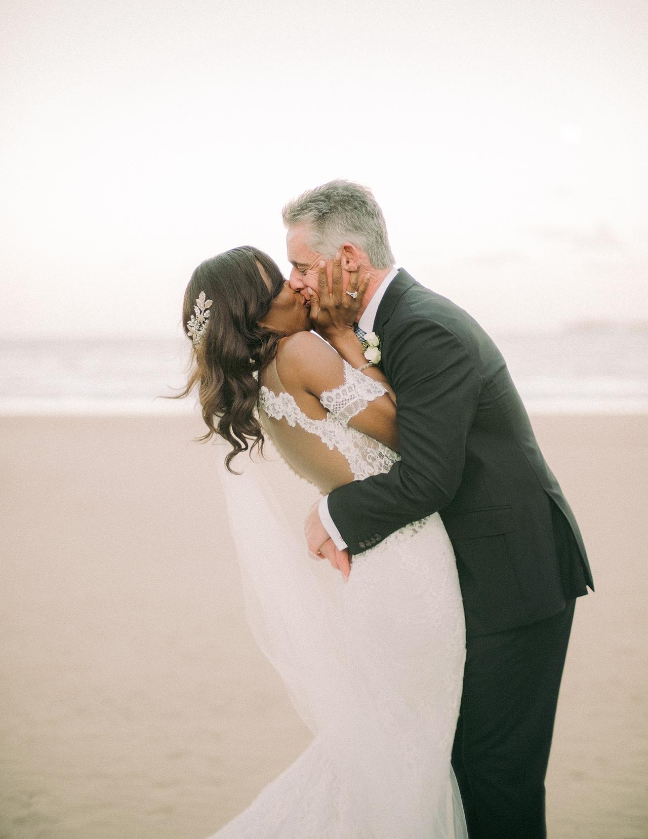 bride groom kiss on beach wedding attire
